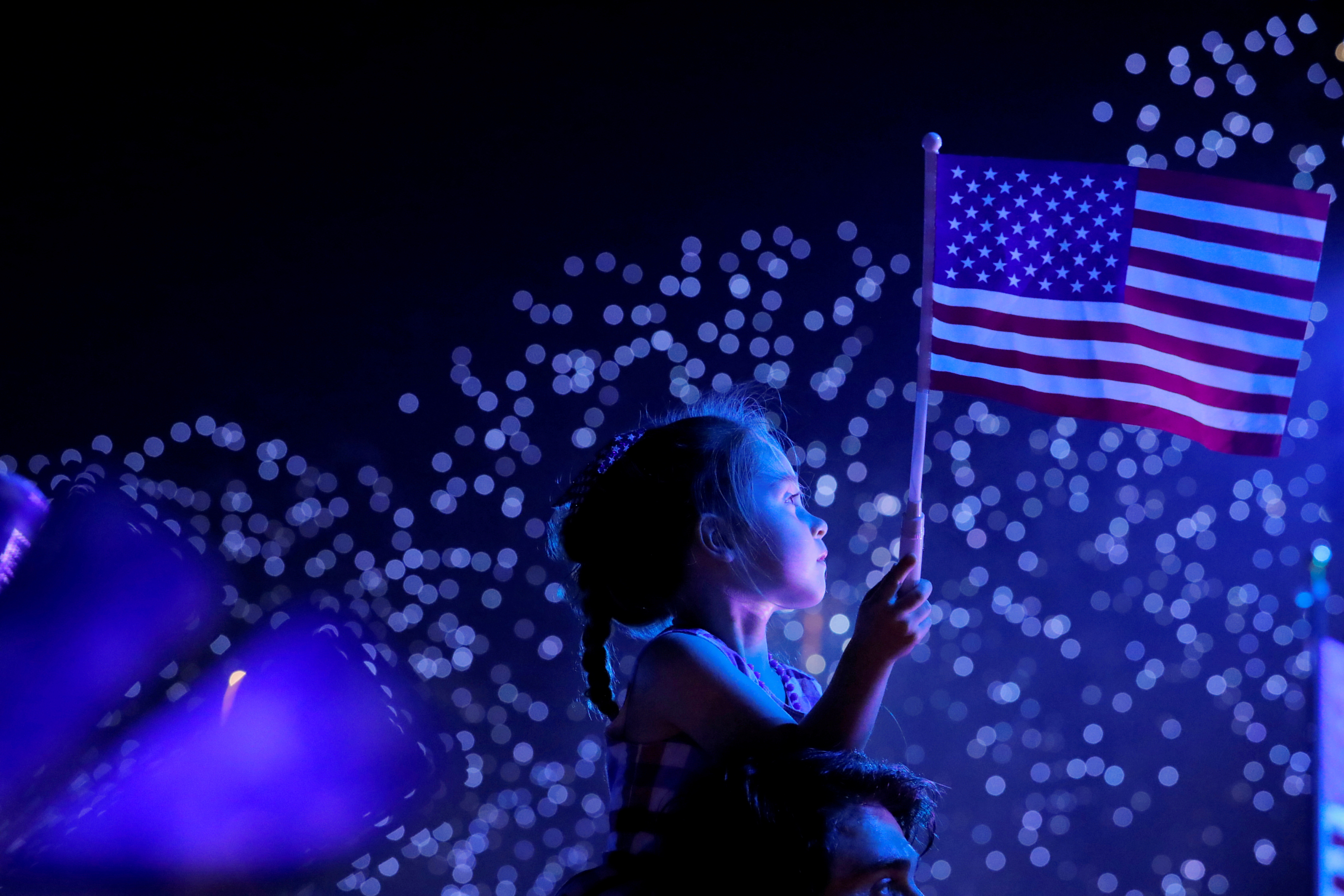 A child watches a Fourth of July fireworks in New York City, while holding an American flag.