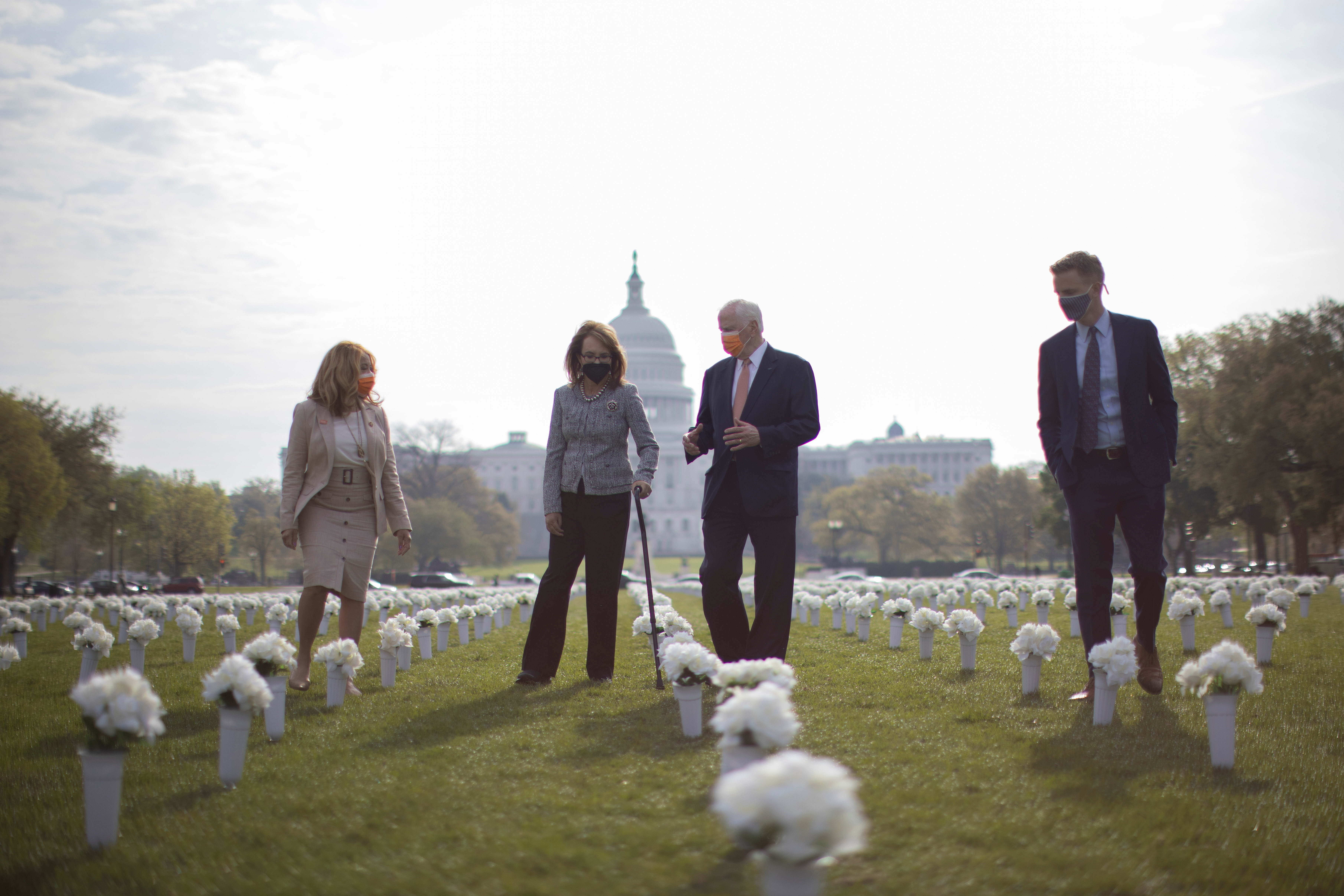 Former U.S. Rep. Gabby Giffords (D-AZ), who resigned her seat in Congress after surviving an assassination attempt, is flanked by U.S. Representatives' Lucy McBath (D-GA) and Mike Thompson (D-CA) as they walk in the new Gun Violence Memorial, an installation featuring 38,000 silk white roses in 4,000 vases to commemorate the roughly 40,000 Americans who die annually in gun violence, on the National Mall in Washington, U.S., April 14, 2021. REUTERS/Carlos Barria? - RC2QVM9QTVKT