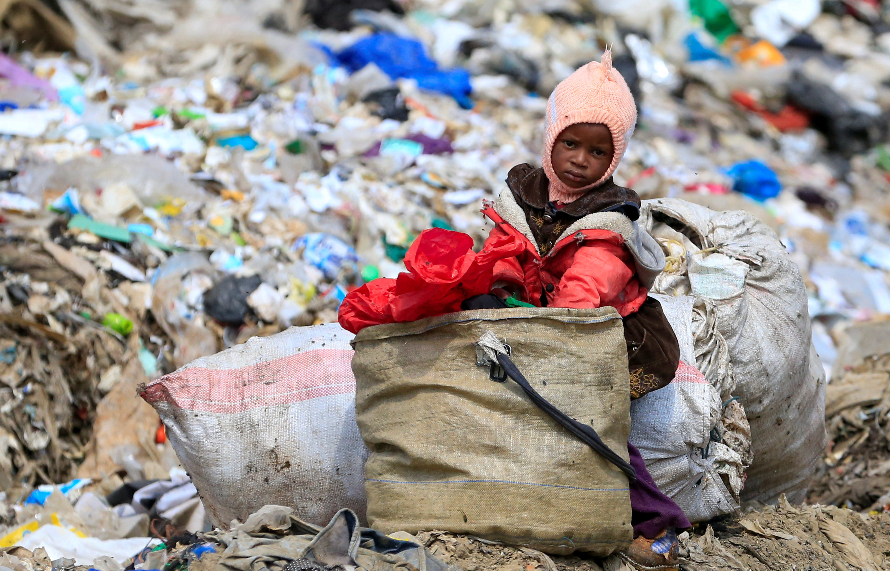 A scavenger's child sits near a bag of collected recyclable waste at the Dandora dumpsite, amid the coronavirus disease (COVID-19) outbreak in Eastlands Nairobi, Kenya July 29, 2020. Picture taken July 29, 2020.
