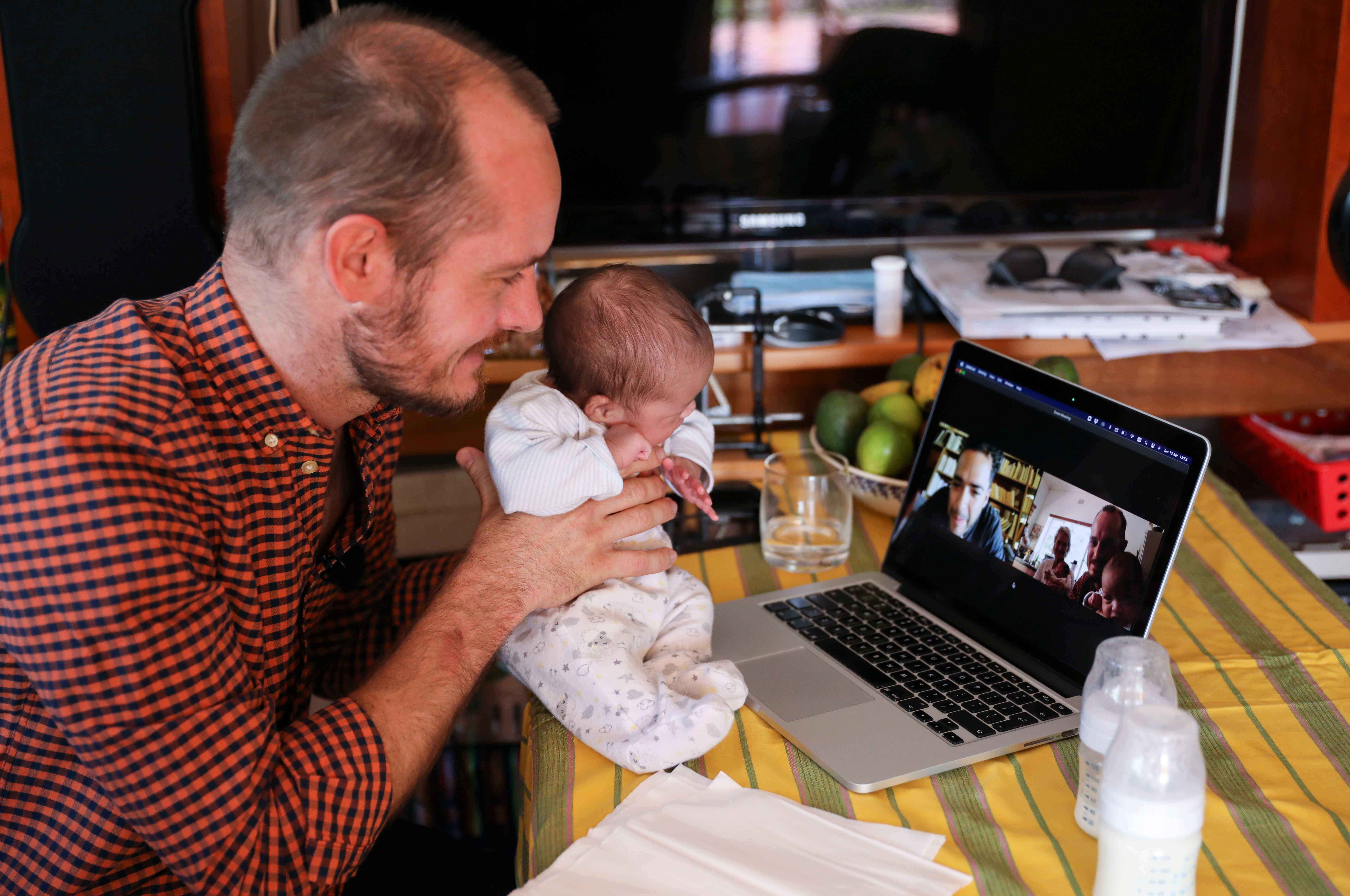 a man shows up a baby on a zoom call