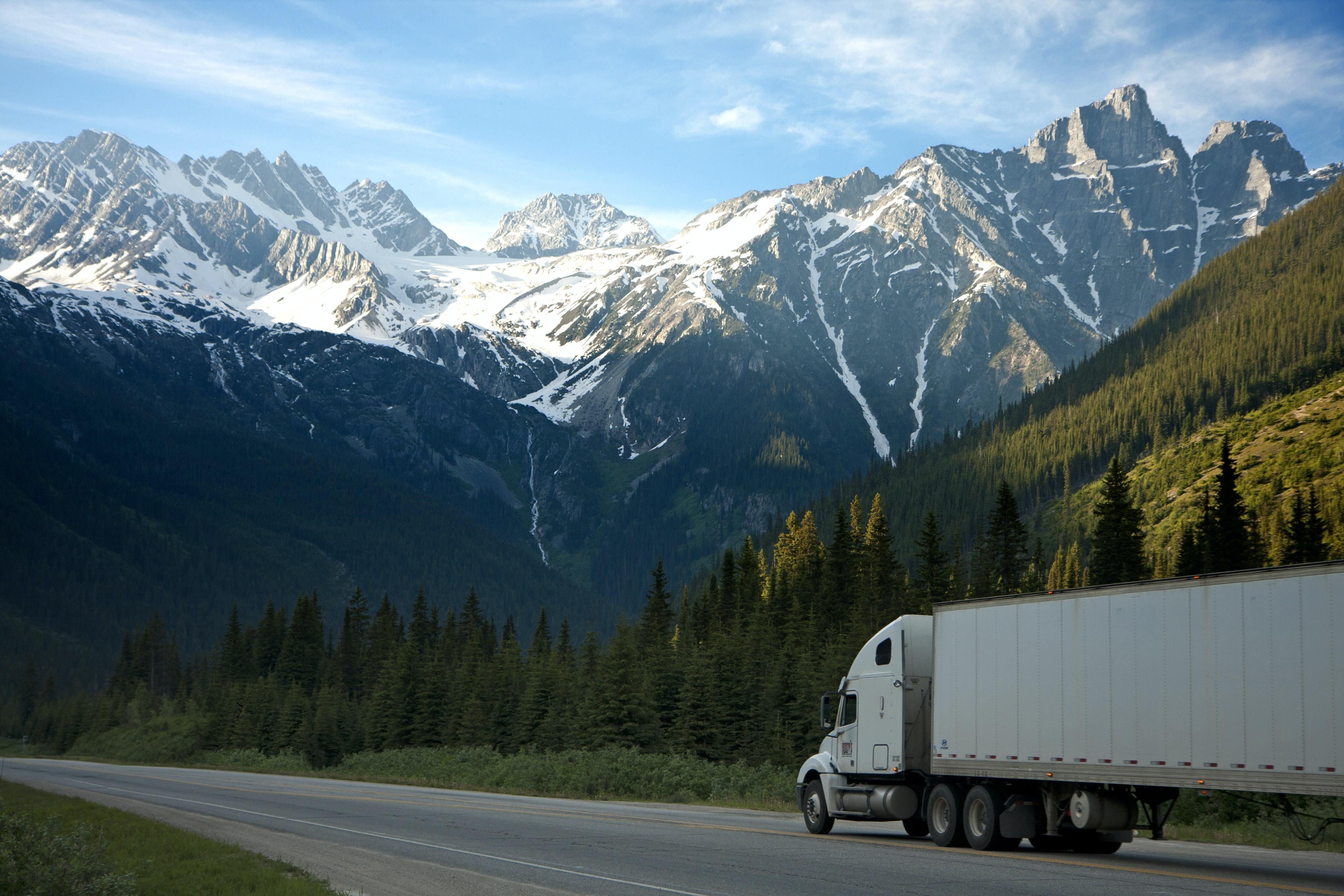Heavy duty truck driving through mountainous landscape.
