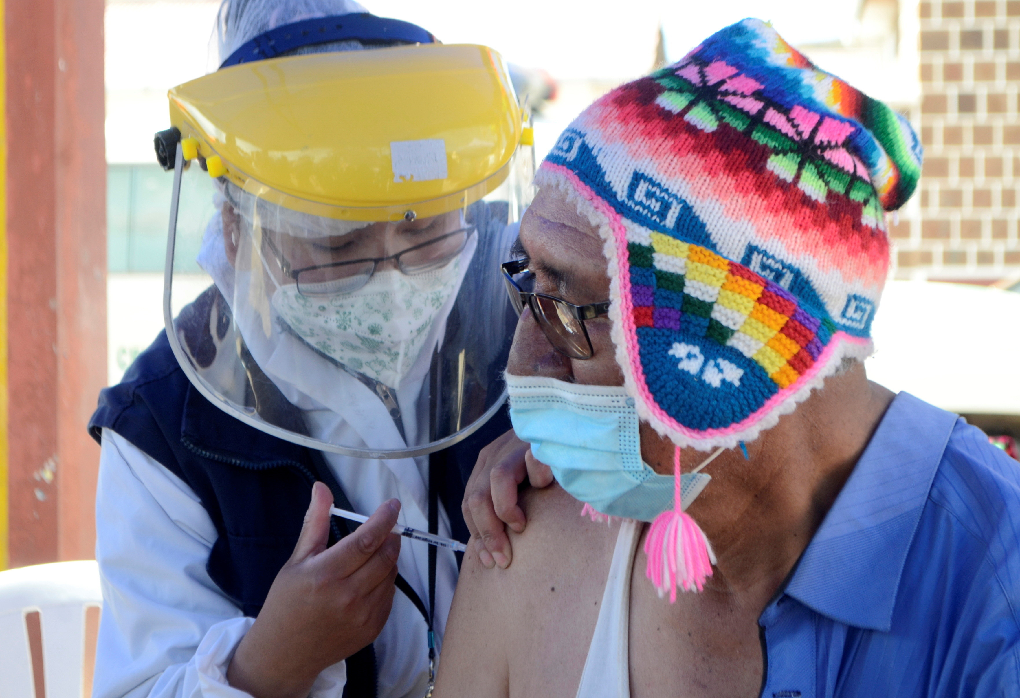 A man in a South-American style hat receives a COVID vaccine.