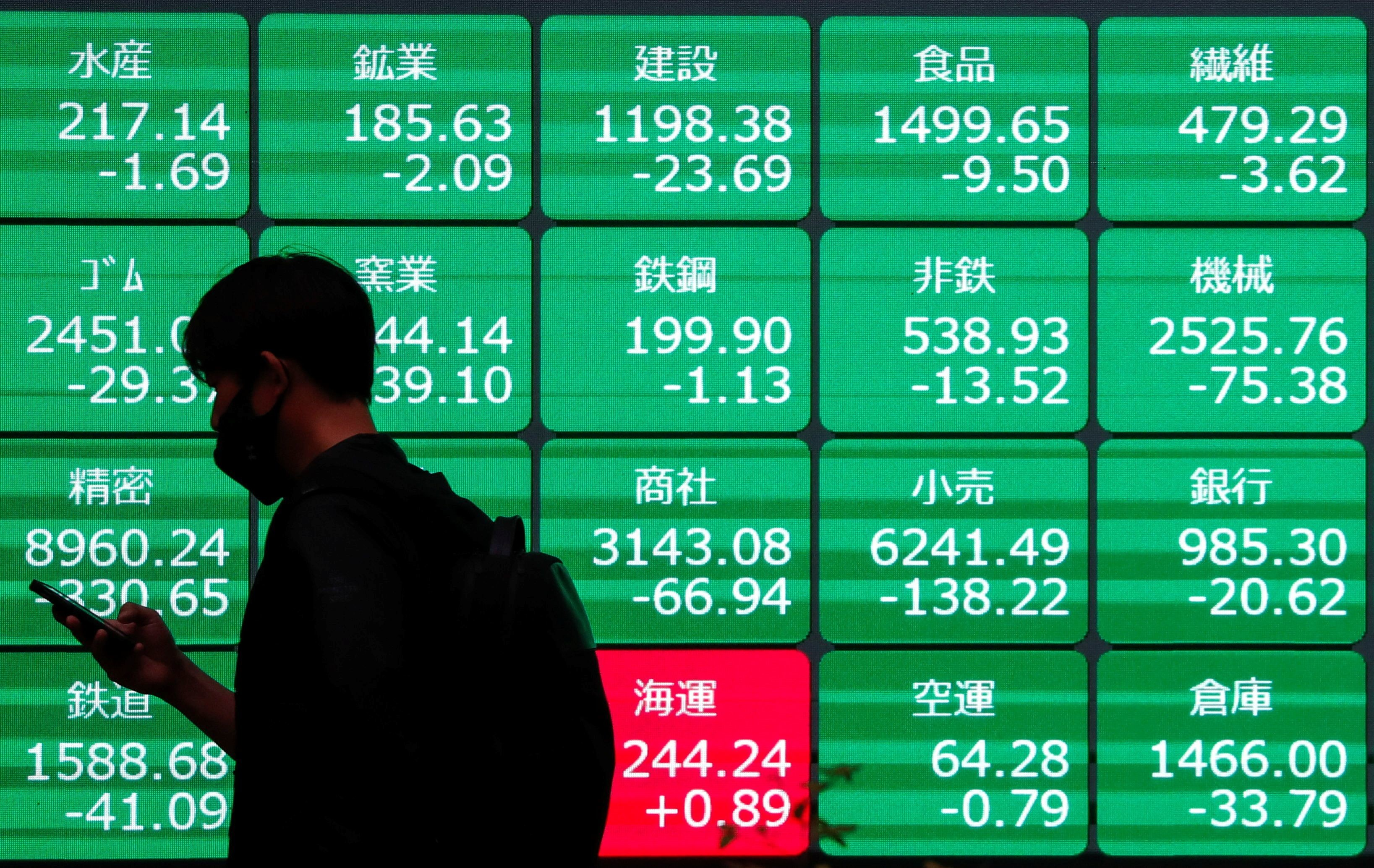 a man walks past a stock brokerage firms window displaying a variety of different stock prices