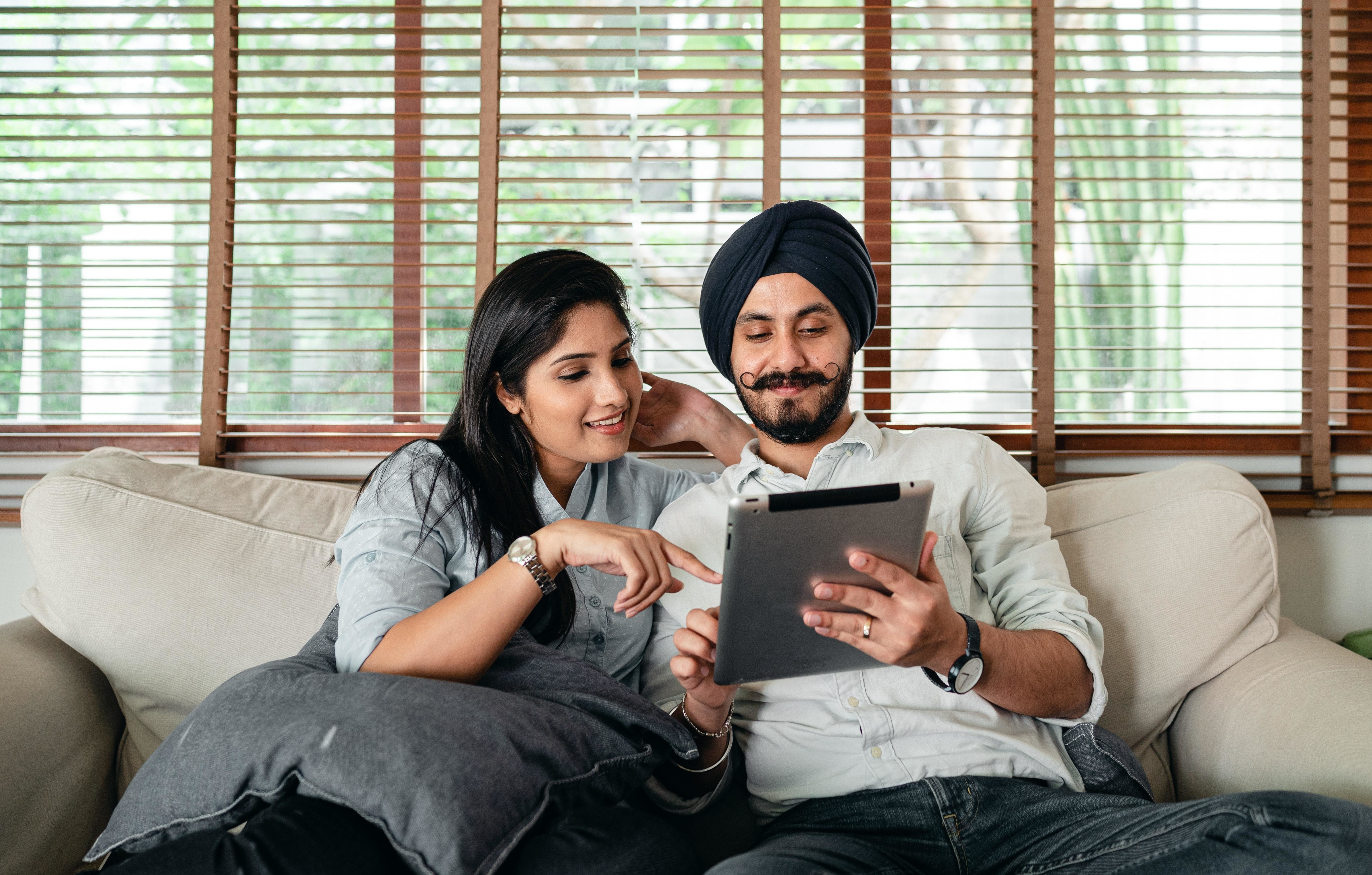 Indian man and women sitting on sofa while looking at electronic tablet.