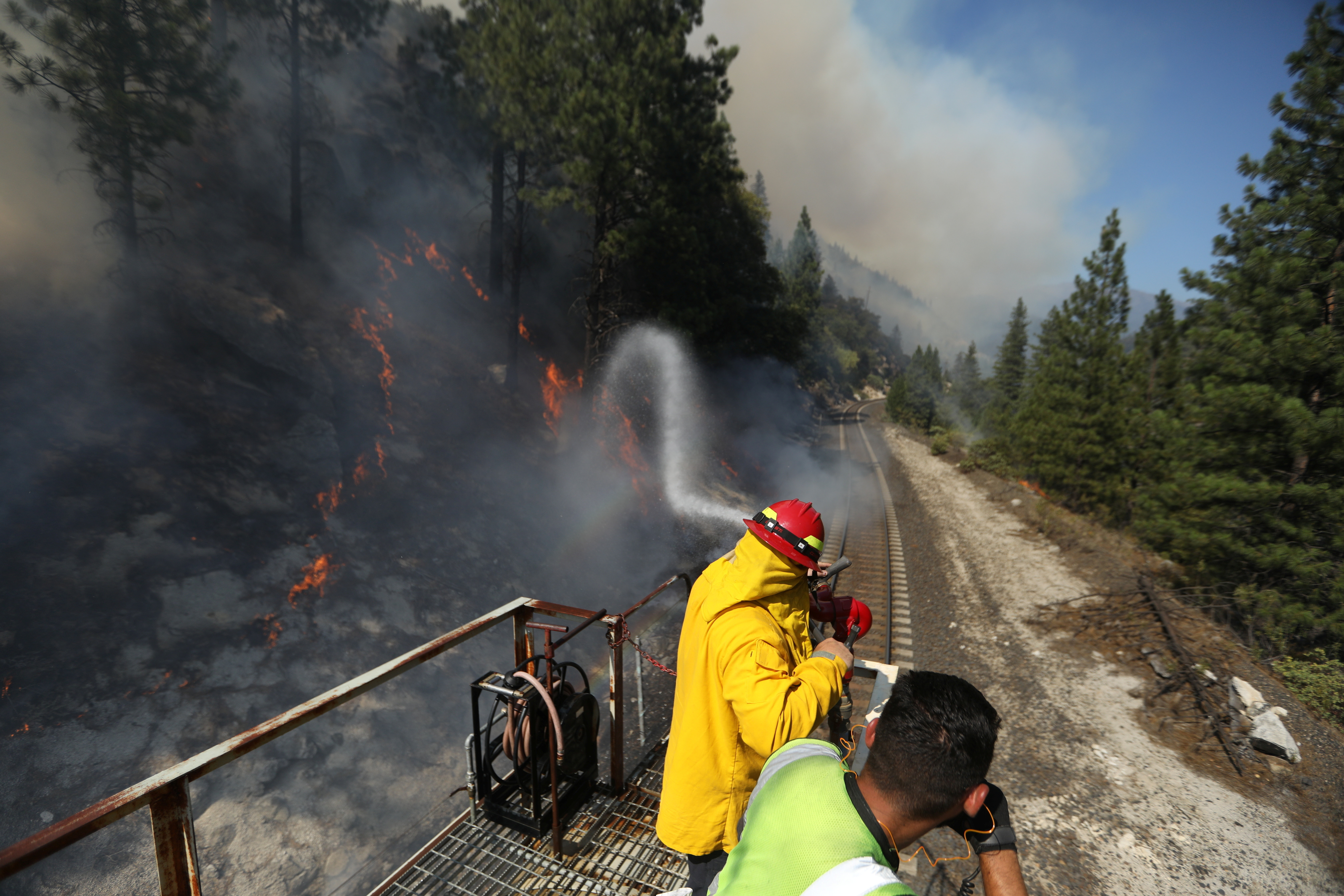 Firefighters assigned to the Union Pacific Fire Train protect the tracks and hinder the Dixie Fire from crossing the North Fork of the Feather River in Plumas National Forest, California, U.S.