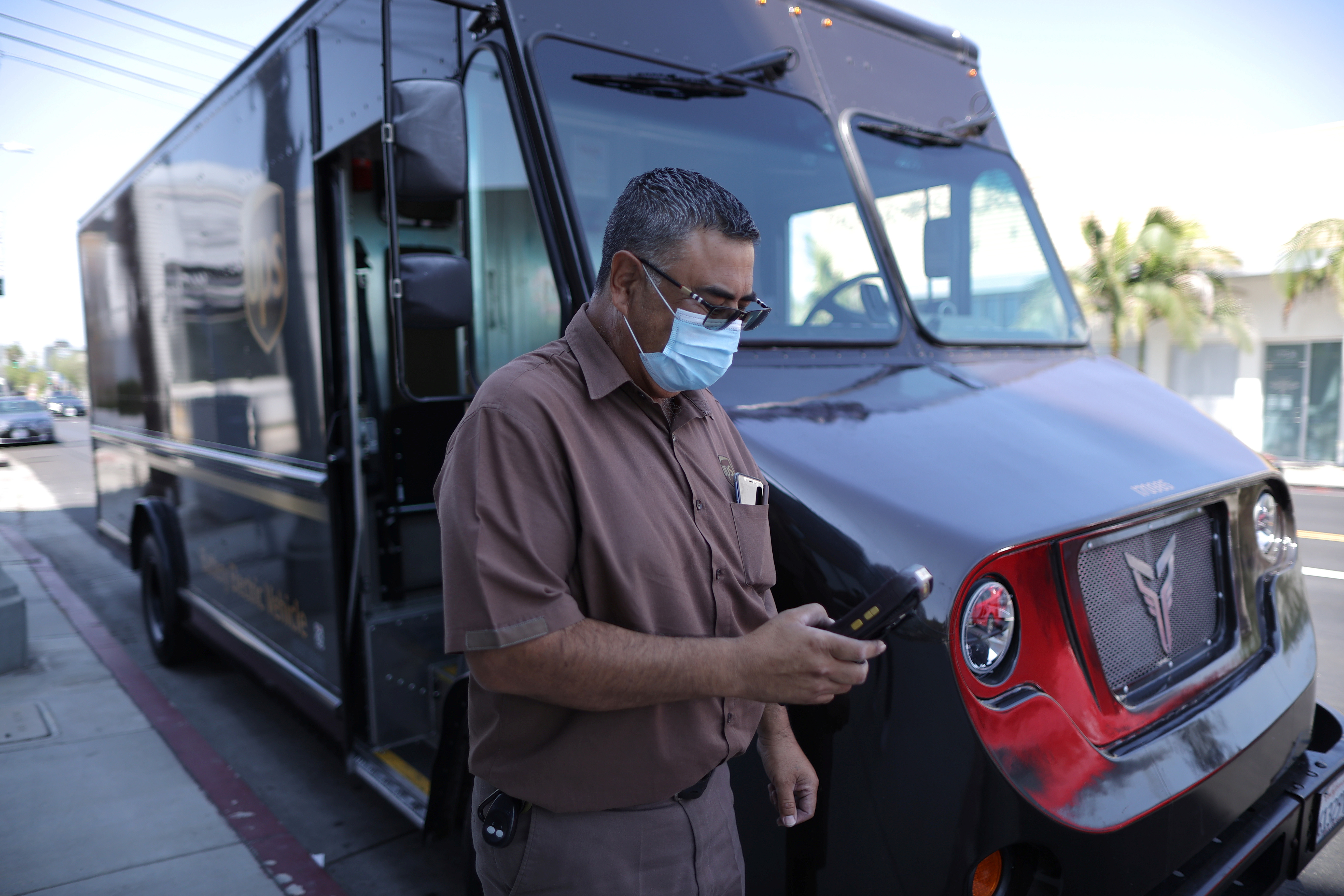 UPS Driver Gilbert Lopez gets out of an electric UPS truck, amid the global outbreak of the coronavirus disease (COVID-19), in Los Angeles, California, U.S., September 1, 2020.  Picture taken September 1, 2020. REUTERS/Lucy Nicholson - RC2YUI99ZE90