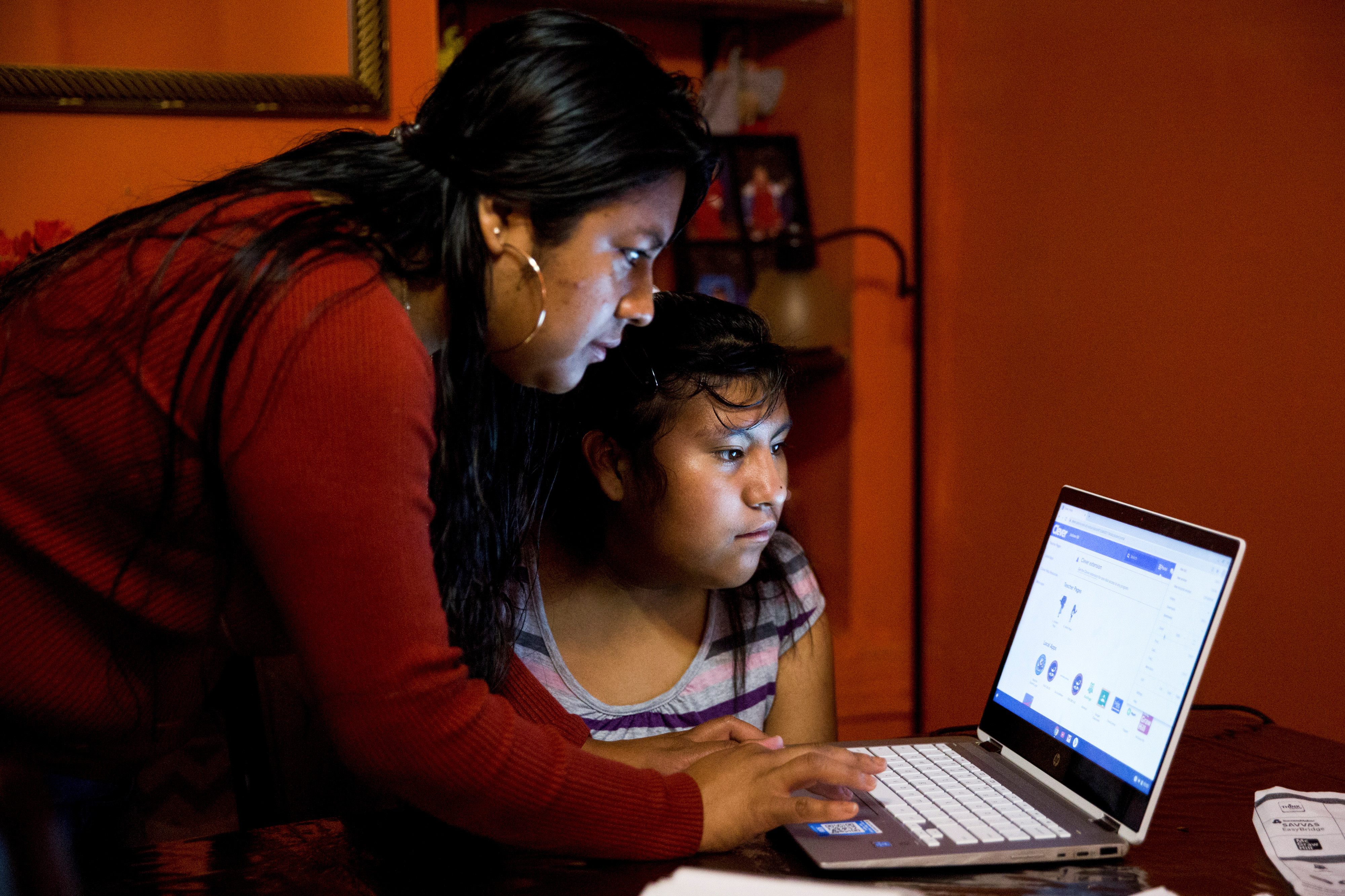 Belen Cruz tries to help her daughter, Natalie, log on to her school's online learning platform at their home in York, Pennsylvania, U.S. September 18, 2020. The online platform would not load for almost an hour, during which Natalie was not able to get any school work done. Picture taken September 18, 2020. REUTERS/Rachel Wisniewski - RC2B8J9V3GRJ