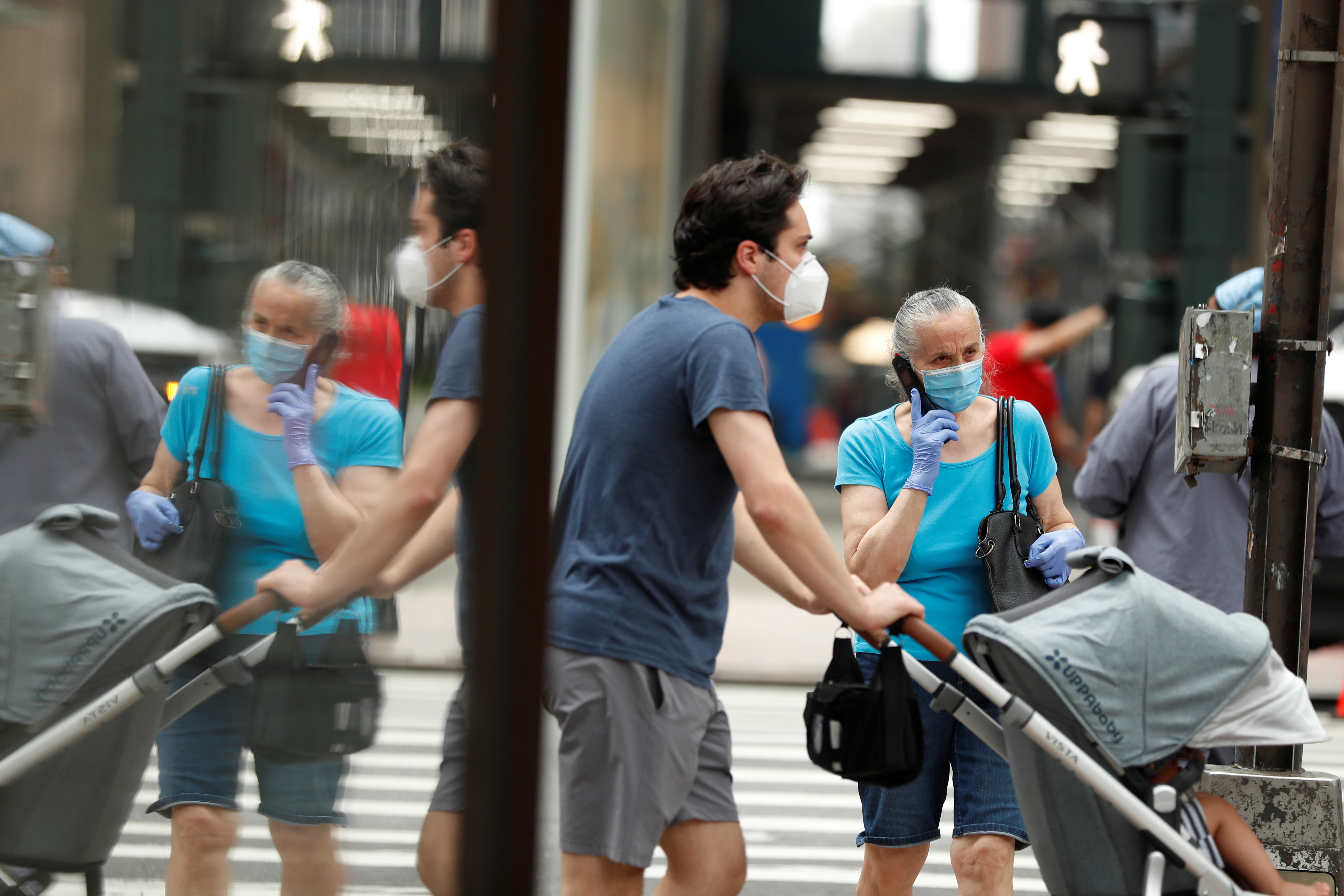 Pedestrians wearing masks walk down the sidewalk  in the Manhattan borough of New York City, U.S., July 1, 2020. REUTERS/Lucas Jackson - RC2HKH9FN7CB