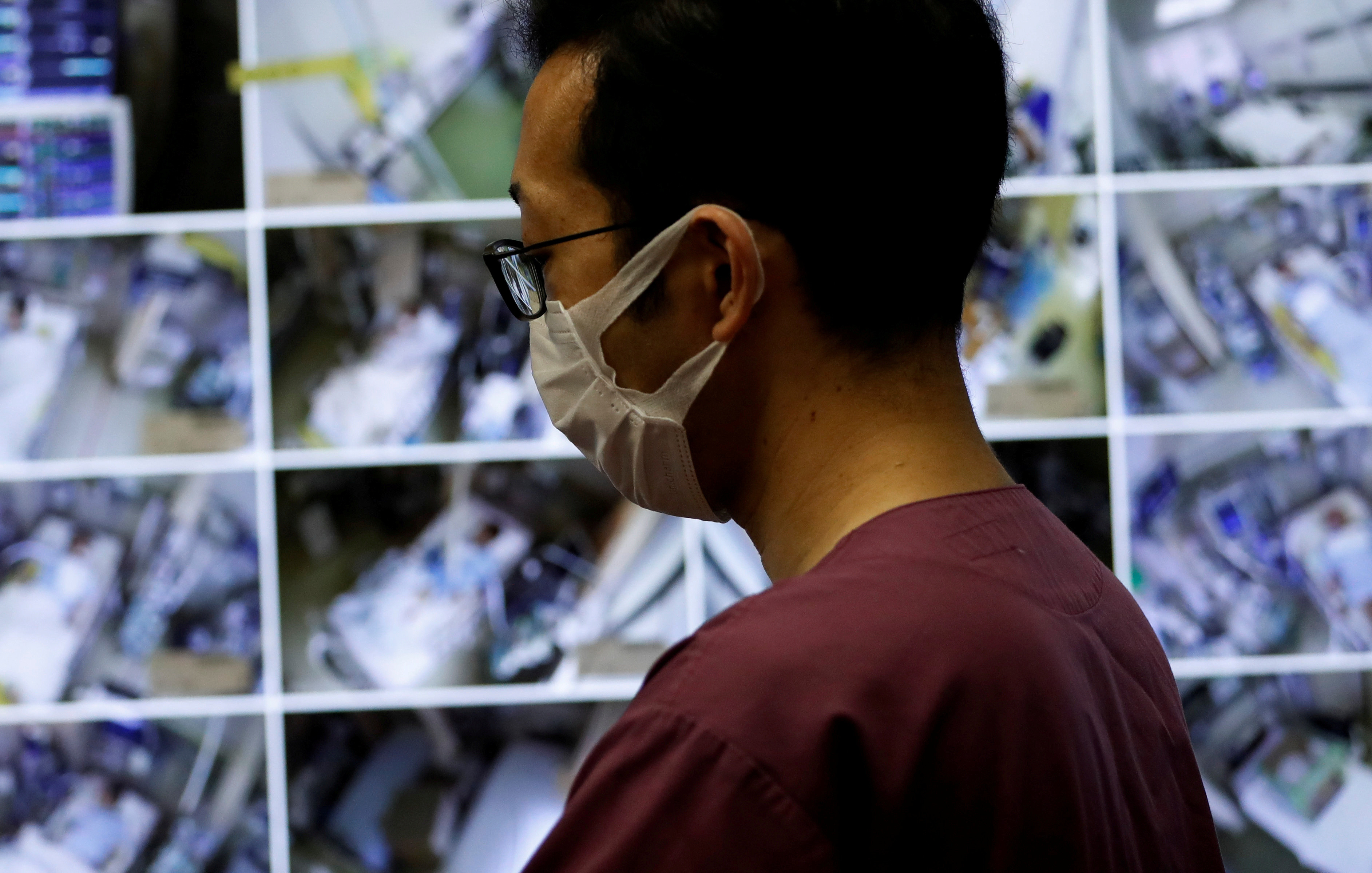 A medical worker wearing a protective face mask monitors remotely the live footages of patients at the Intensive Care Unit (ICU) ward for coronavirus disease (COVID-19) patients at St. Marianna Medical University Hospital in Kawasaki, south of Tokyo, Japan May 4, 2020.  REUTERS/Issei Kato     TPX IMAGES OF THE DAY - RC2GHG9P1REO