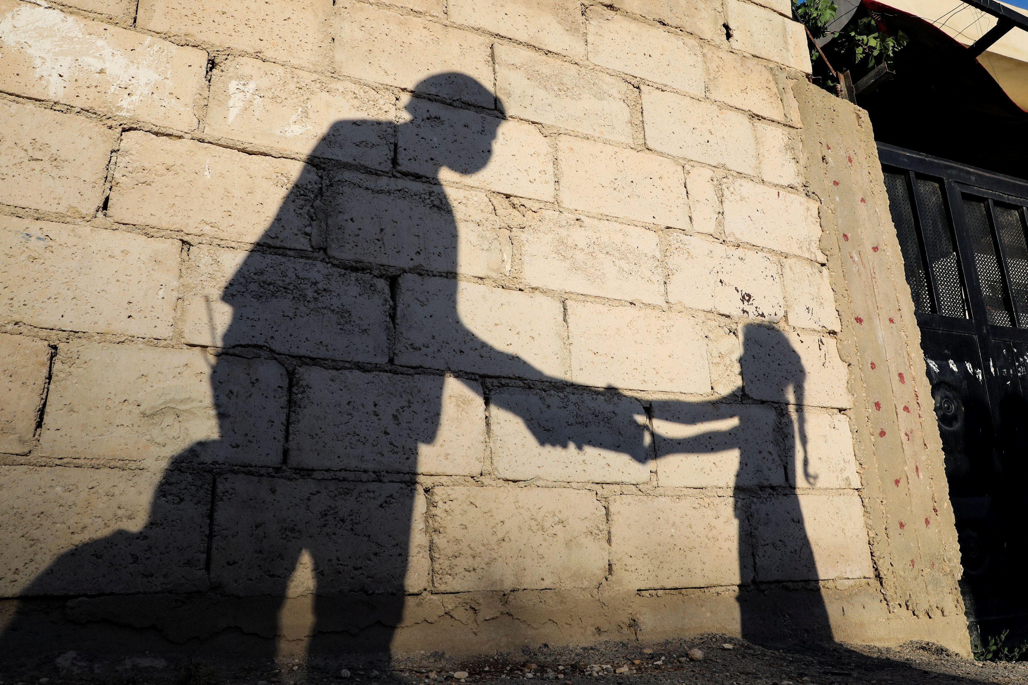 "The shadow of a girl receiving a meal for iftar, or the evening meal, to break fast from a member of ""Tkiyet Um Ali"" humanitarian services center is cast on a wall in front of her family home in the city of Russeifa, during the holy fasting month of Ramadan, amid concerns over the spread of coronavirus disease (COVID-19), in Jordan, April 28, 2020. Picture taken April 28, 2020. REUTERS/Muhammad Hamed     TPX IMAGES OF THE DAY - RC2ZDG987UP8"