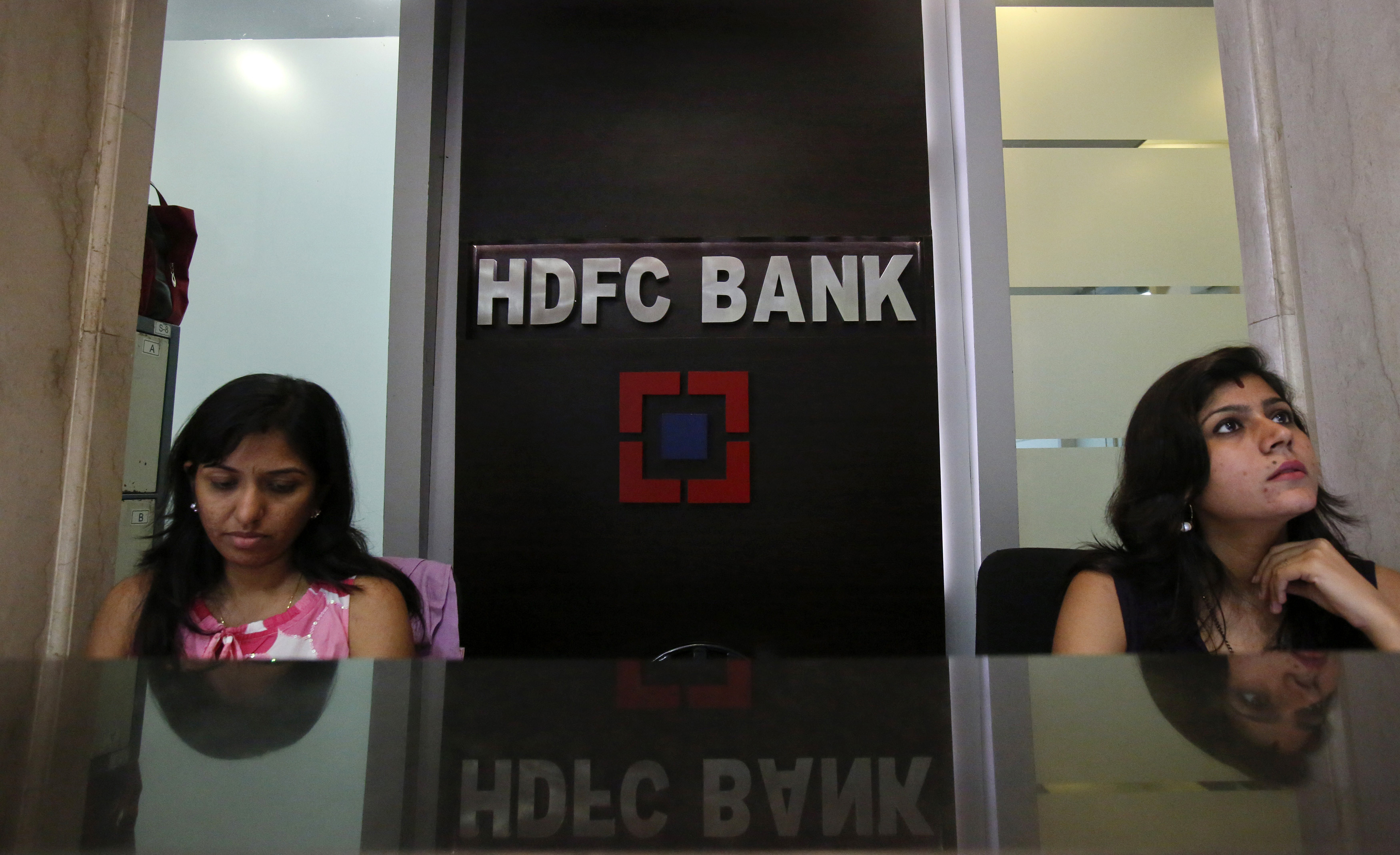 Personal bankers wait for customers at the reception of a HDFC Bank branch in Mumbai November 17, 2012.
