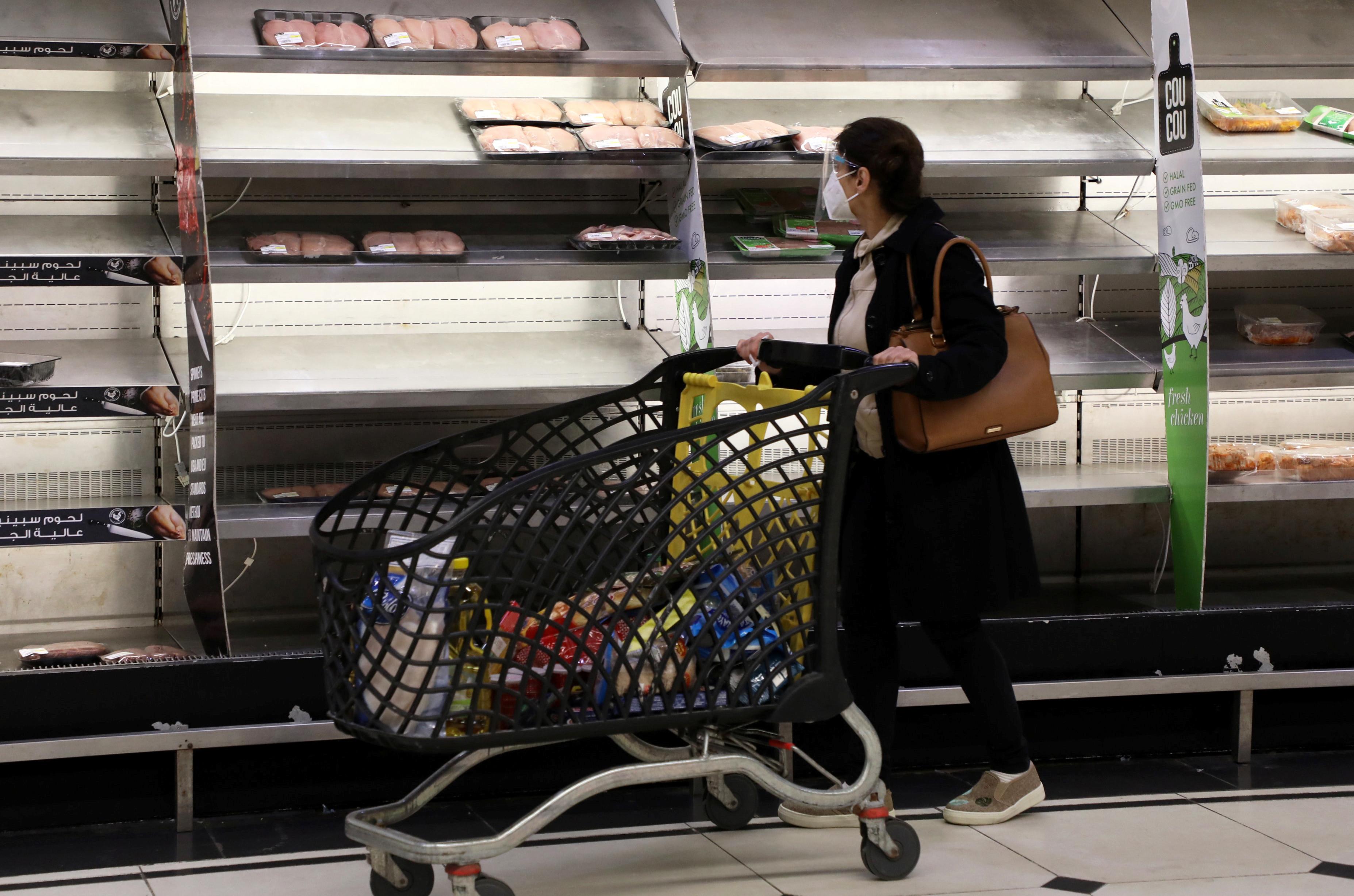 A shopper walks past near-empty shelves at a supermarket in Beirut, Lebanon