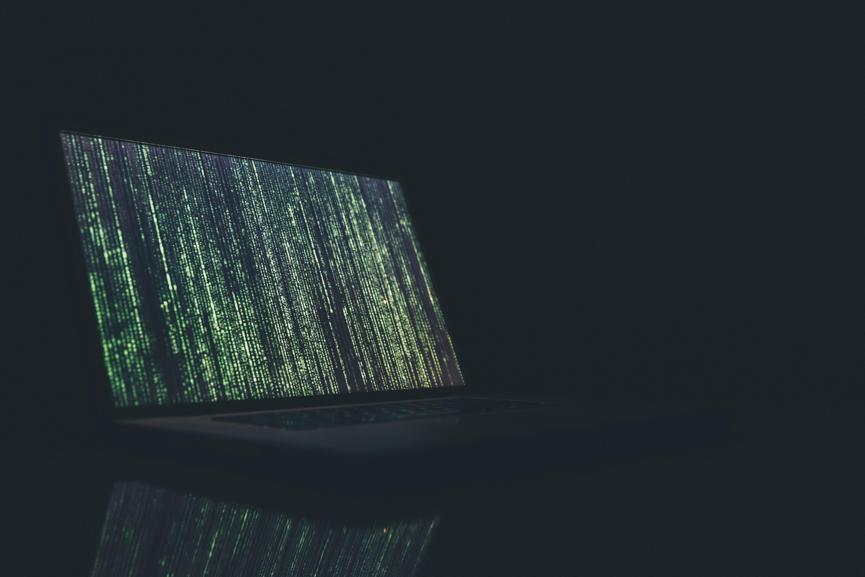 Open laptop, dark room; cybercrime, security, ransomware, disinformation, dark web, digitalization, technology