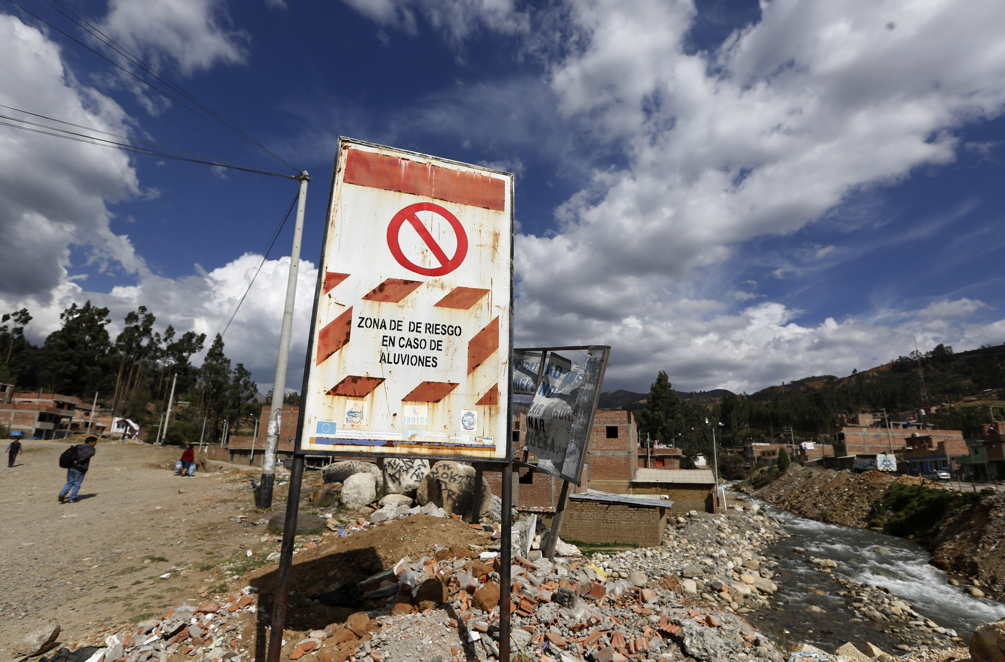 """A sign reading, """"Risk area of floods"""" near a town in Huaraz, Peru."""
