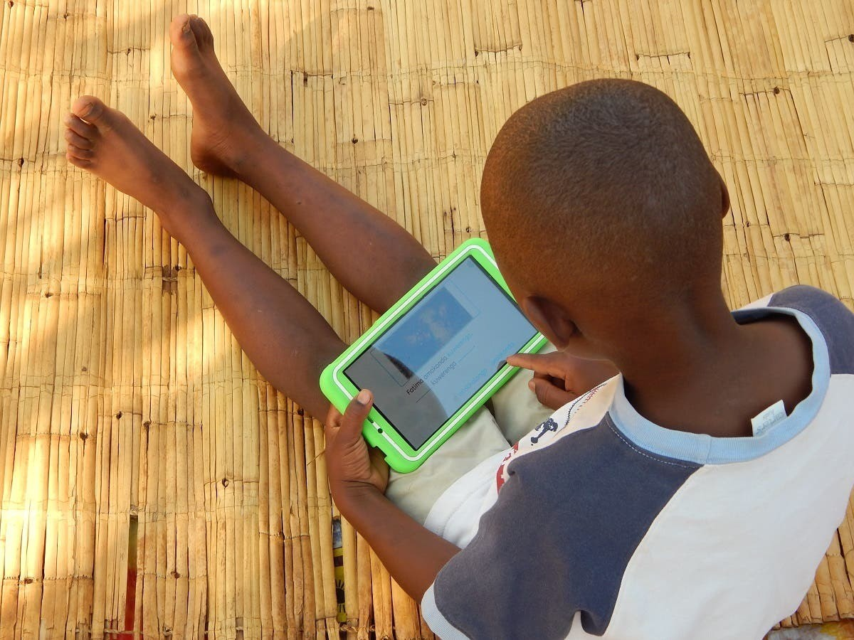 Eight-year-old Elijah Chiseka uses a learning tablet provided by the charity Voluntary Service Overseas in Gumulira village in western Malawi, September 23, 2020.