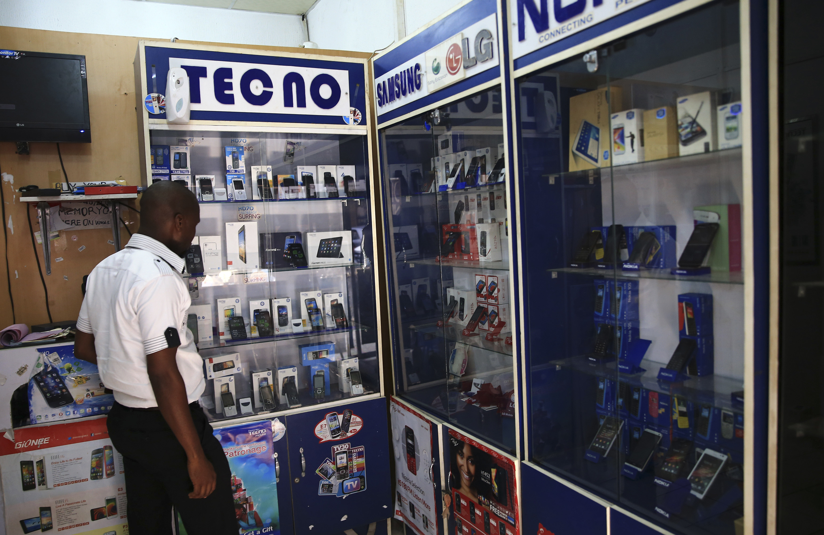 A man looks at smartphones on display at a shop at Wuse II business district in Abuja December 9, 2014. Nigeria is suffering from a plummeting currency, steep budget cuts, corruption scandals and diving oil prices; yet all this is unlikely to decide a tight race for the presidency. When the central bank devalued the naira last month to save foreign reserves, the impact was felt instantly on the streets. Nigeria imports 80 percent of what it consumes. Picture taken December 9, 2014.    REUTERS/Afolabi Sotunde  (NIGERIA - Tags: BUSINESS POLITICS) - GM1EACF16MS01