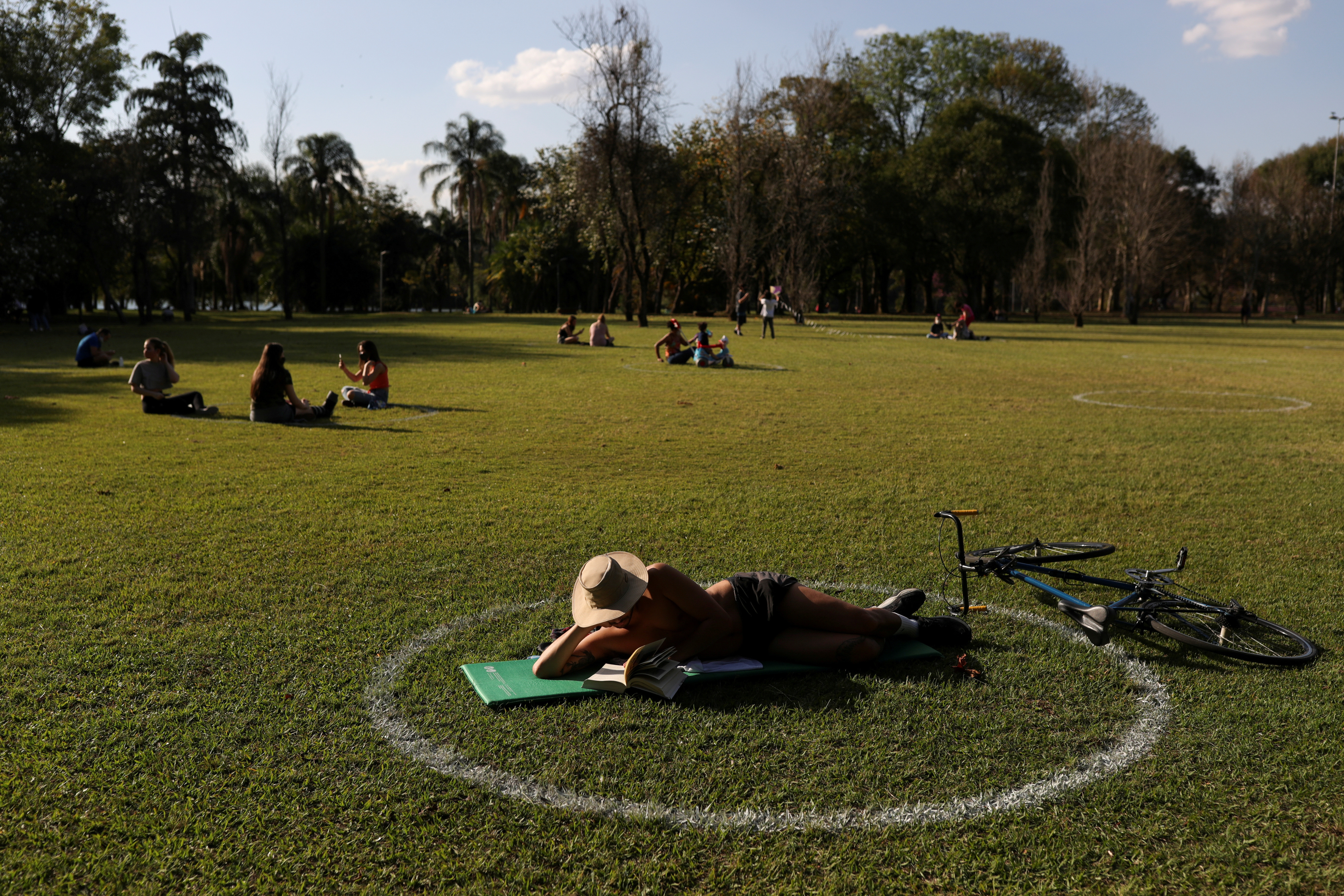 A man reads as he lies in a field where circles were painted to help visitors maintain social distancing at Ibirapuera Park after it was reopened as the city eases the restrictions imposed to control the spread of the coronavirus disease (COVID-19), in Sao Paulo, Brazil July 13, 2020. REUTERS/Amanda Perobelli     TPX IMAGES OF THE DAY - RC2JSH94FV6X