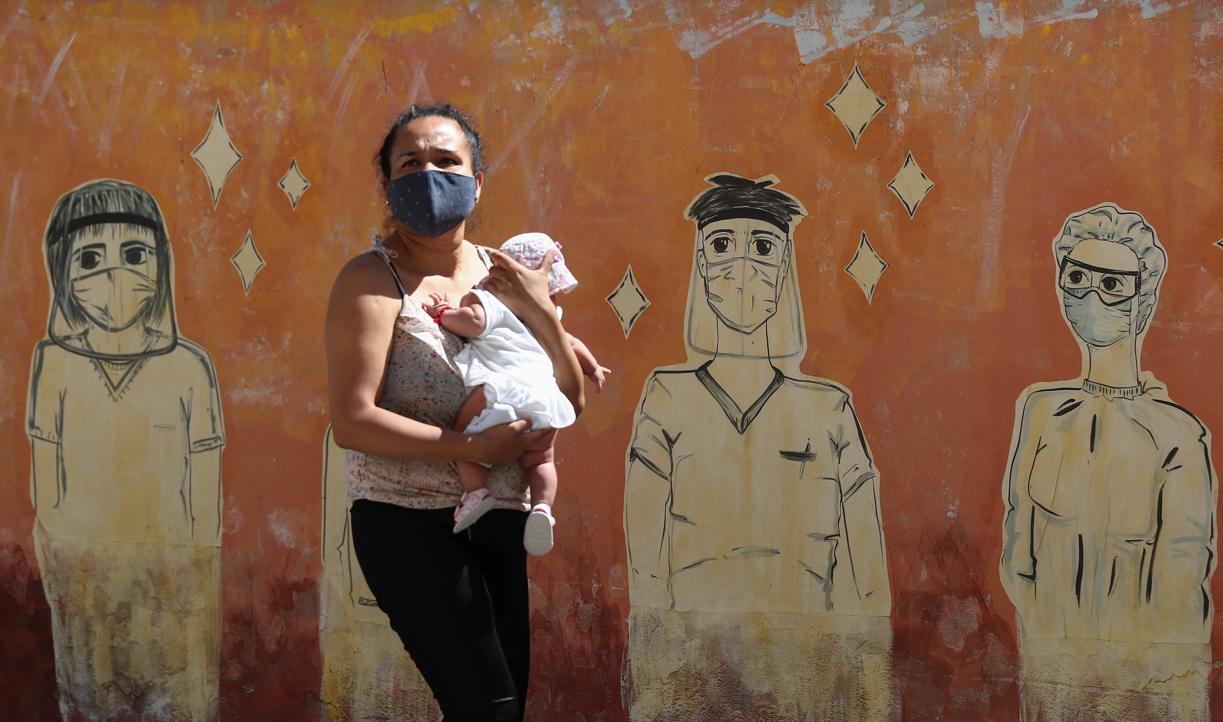 A woman wearing a face mask to prevent the spread of the coronavirus disease (COVID-19) walks past a graffiti in homage to the medical staff, at the San Martin hospital, in La Plata, on the outskirts of Buenos Aires, Argentina January 21, 2021.