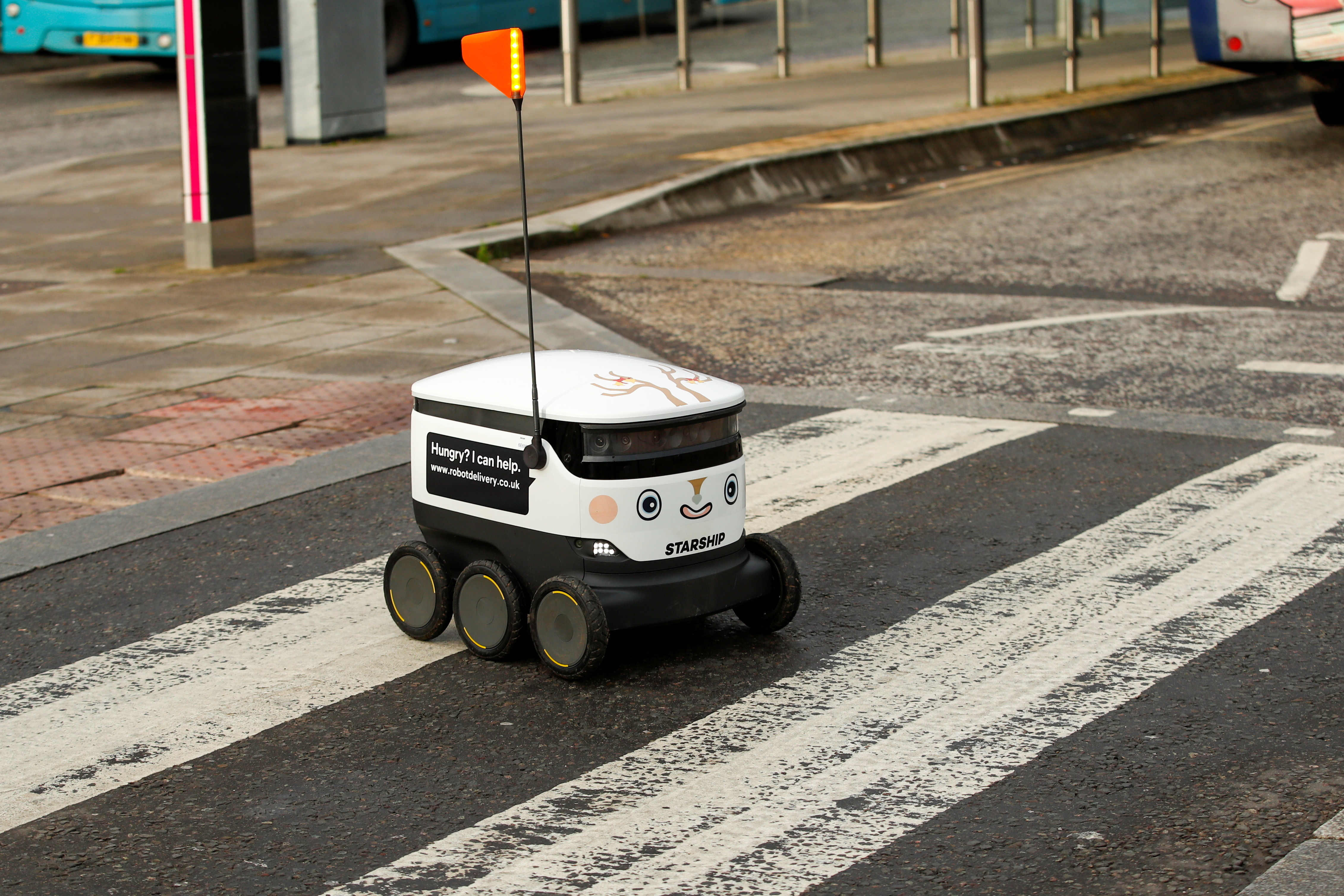 A Starship delivery robot crosses a street amid the coronavirus disease (COVID-19) outbreak, in Milton Keynes, Britain, December 16, 2020. REUTERS/Andrew Boyers - RC2COK9QLPDL