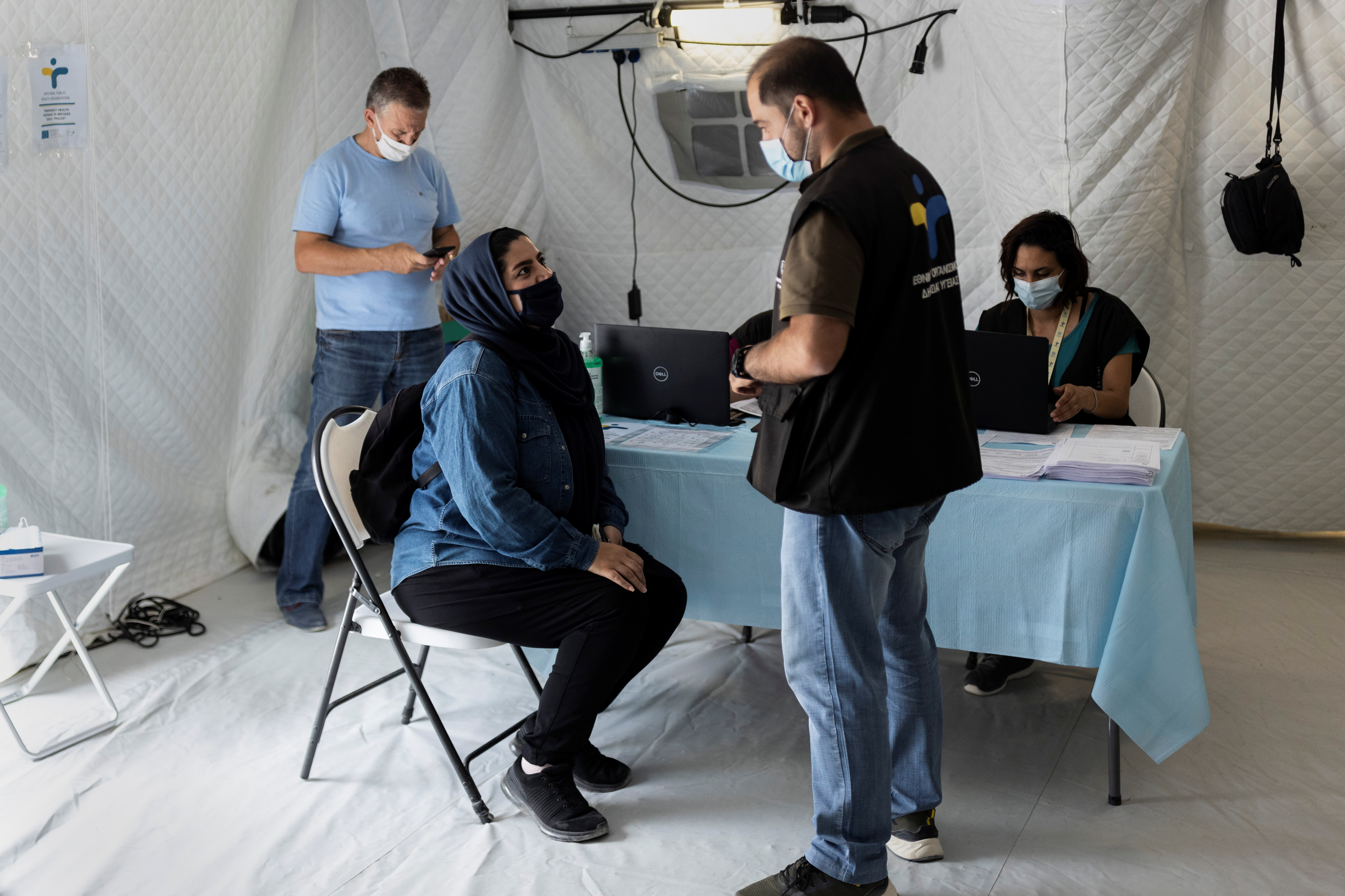 A migrant speaks with a Health ministry official before receiving a shot of the vaccine against the coronavirus disease