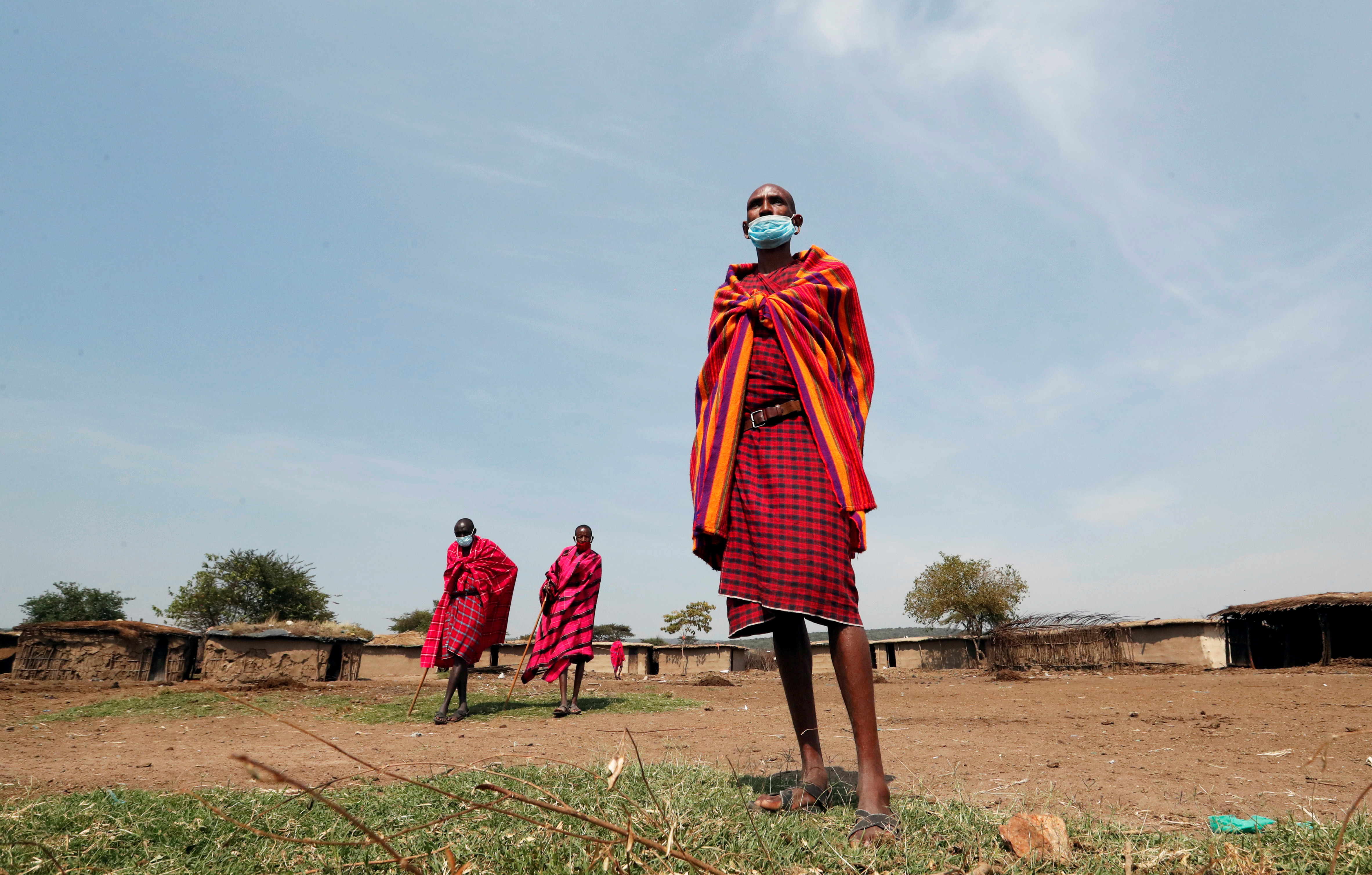Maasai elders, wearing traditional costumes, with face masks on, due to the coronavirus disease (COVID-19) outbreak, gather at their homestead within the Orboma Manyatta in Sekenani, near the Maasai Mara game reserve in Narok County, Kenya August 10, 2020. REUTERS/Thomas Mukoya     TPX IMAGES OF THE DAY - RC25BI9LUIHN