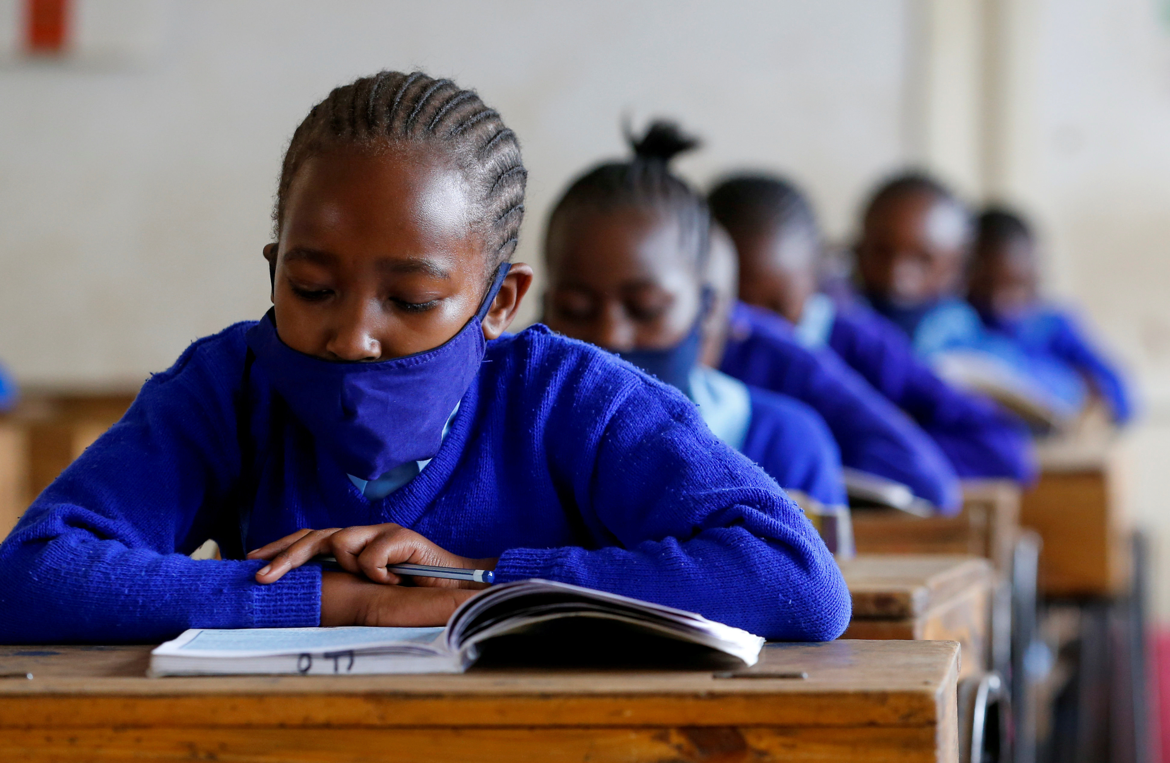 A schoolgirl wears a face mask as she reads a book inside a classroom at the Olympic Primary School during the partial reopening of schools, after the government scrapped plans to cancel the academic year due to the coronavirus disease (COVID-19) pandemic, in Kibera slums of Nairobi, Kenya October 12, 2020. REUTERS/Thomas Mukoya - RC2WGJ9PLMPT
