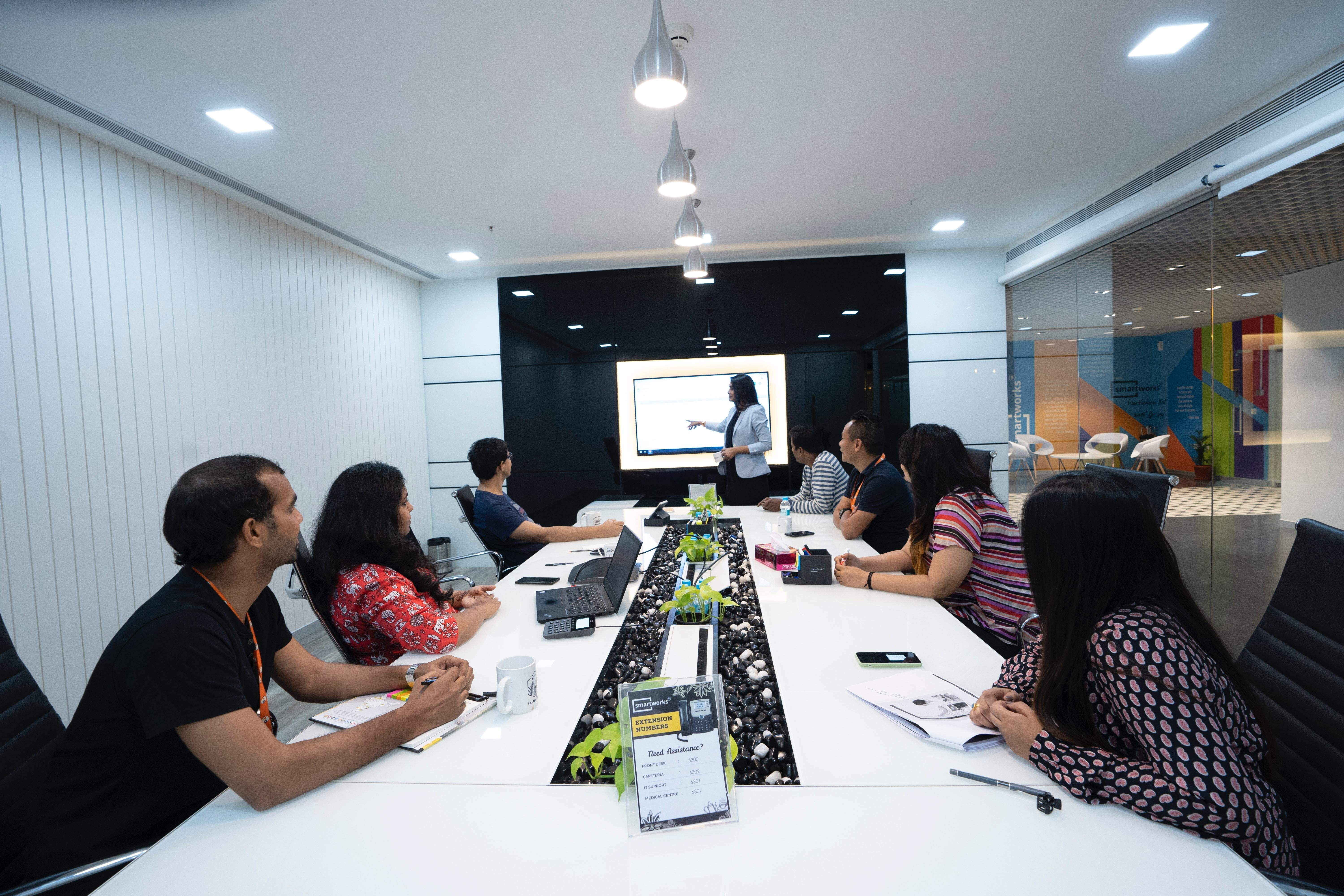 A team of people in a meeting room look towards a presenter; business, entrepreneurs, digitalisation.
