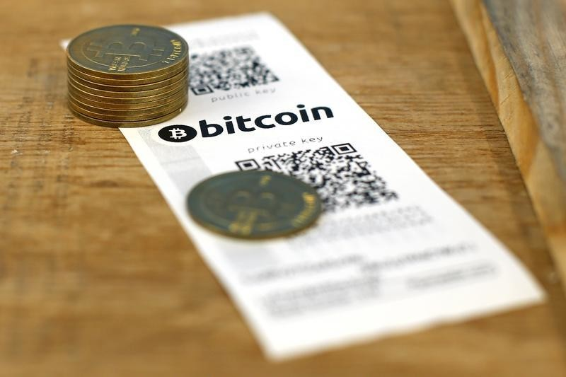 A Bitcoin (virtual currency) paper wallet with QR codes and coins are seen in an illustration picture taken at La Maison du Bitcoin in Paris July 11, 2014. French police dismantled an illegal Bitcoin exchange and seized 388 virtual currency units worth some 200,000 euros ($272,800) in the first such operation in Europe a public prosecutor said on Monday.   REUTERS/Benoit Tessier (FRANCE - Tags: BUSINESS) - RTR3Y7O4