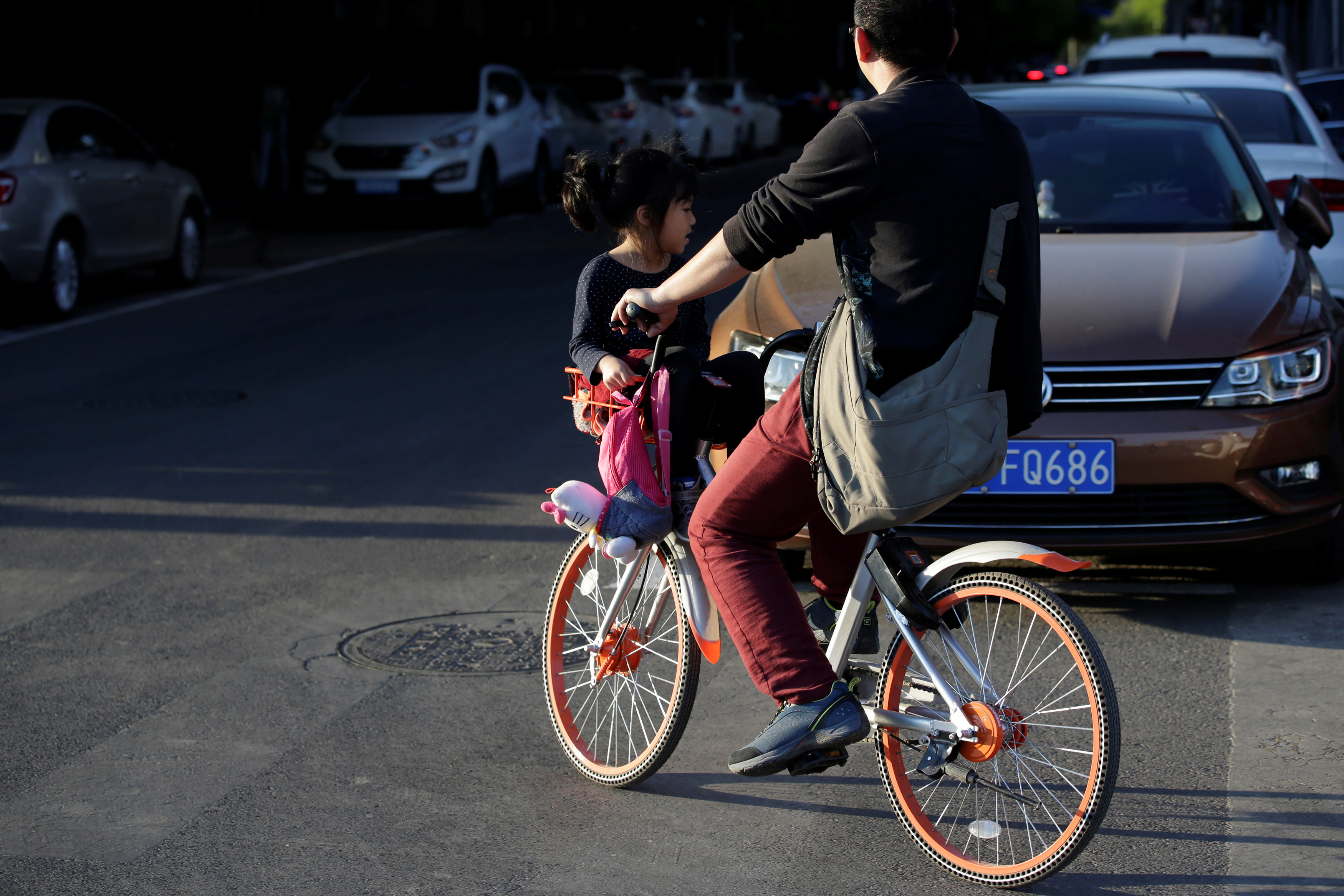A man rides a Mobike's shared bike to carry a girl in bicycle basket on a road in Beijing, China April 21, 2017. Picture taken April 21, 2017. REUTERS/Jason Lee - RTS16B80