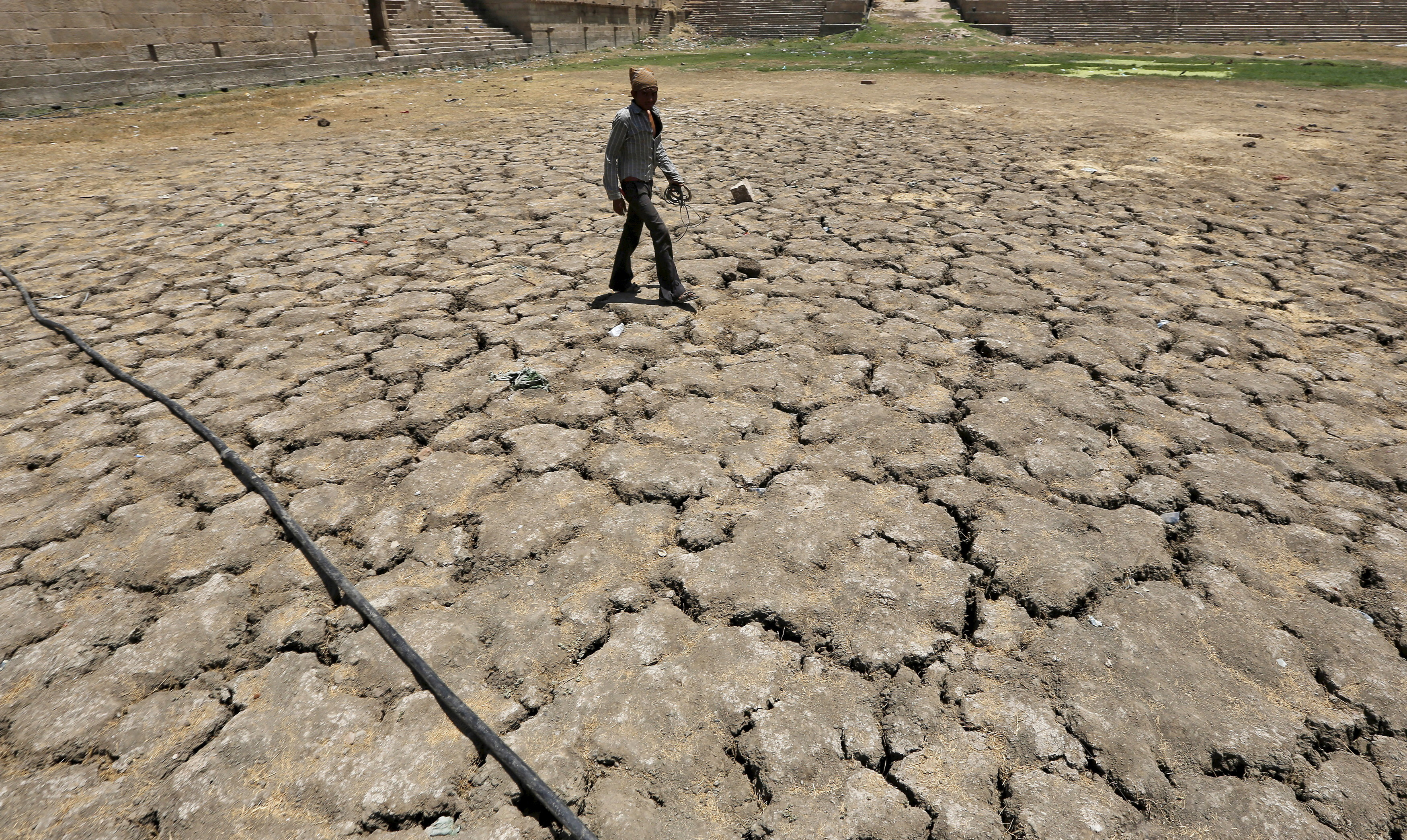 A man walks through a dried-up Sarkhej lake on a hot summer day in Ahmedabad.
