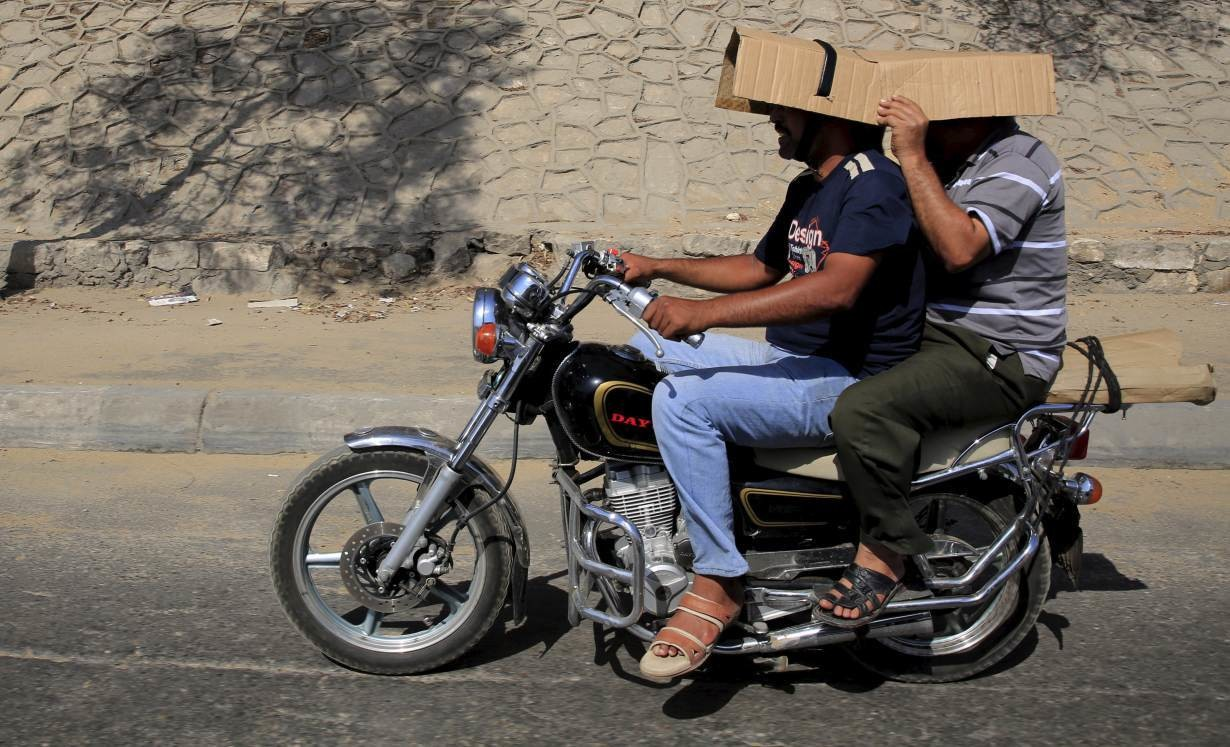 Men cover their heads from the sun while riding on a motorcycle during a hot day in Cairo, Egypt,  August 17, 2015.