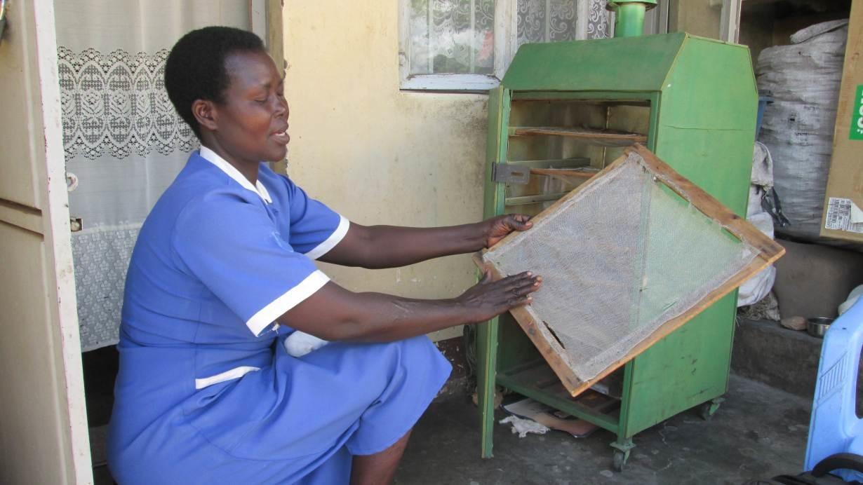 Nurse and farmer Christine Anek explains how she uses her eco-friendly food dryer in Pader district, northern Uganda, May 21, 2019. Thomson Reuters Foundation/John Okot