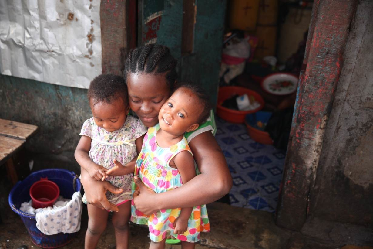 Fatmata, 20, holds her twin daughters outside her home in Susan's Bay, Freetown, Sierra Leone. July 24, 2019.