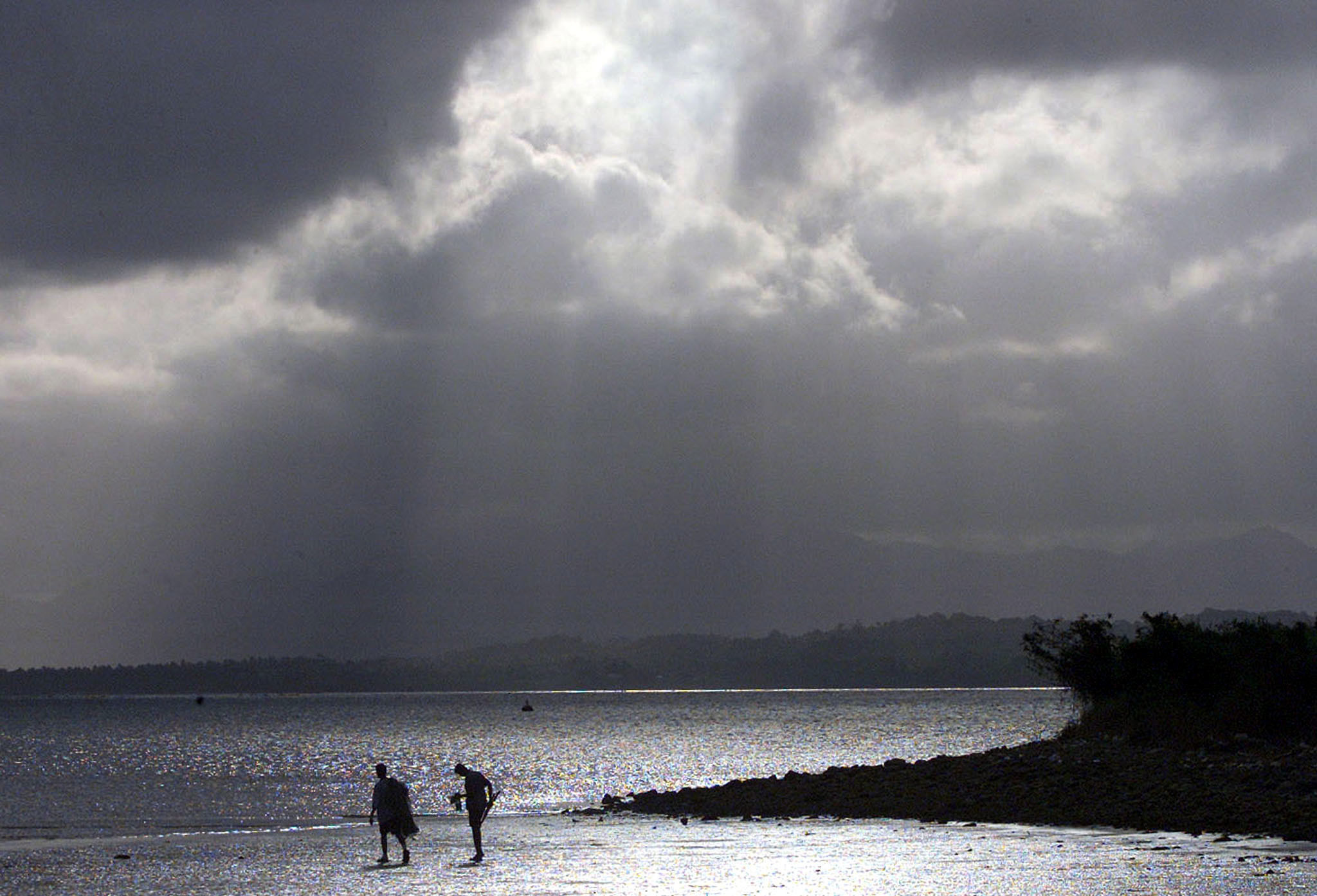 An afternoon storm looms above fishermen on the mud flats of a Suva beach September 9, 2001. [Fiji's general election has ended after a week of polling with caretaker Prime Minister Laisenia Qarase expected to approach Fiji's president form a majority coalition government after negotiations with minor parties on September 10, 2001.] - RTXKQTG
