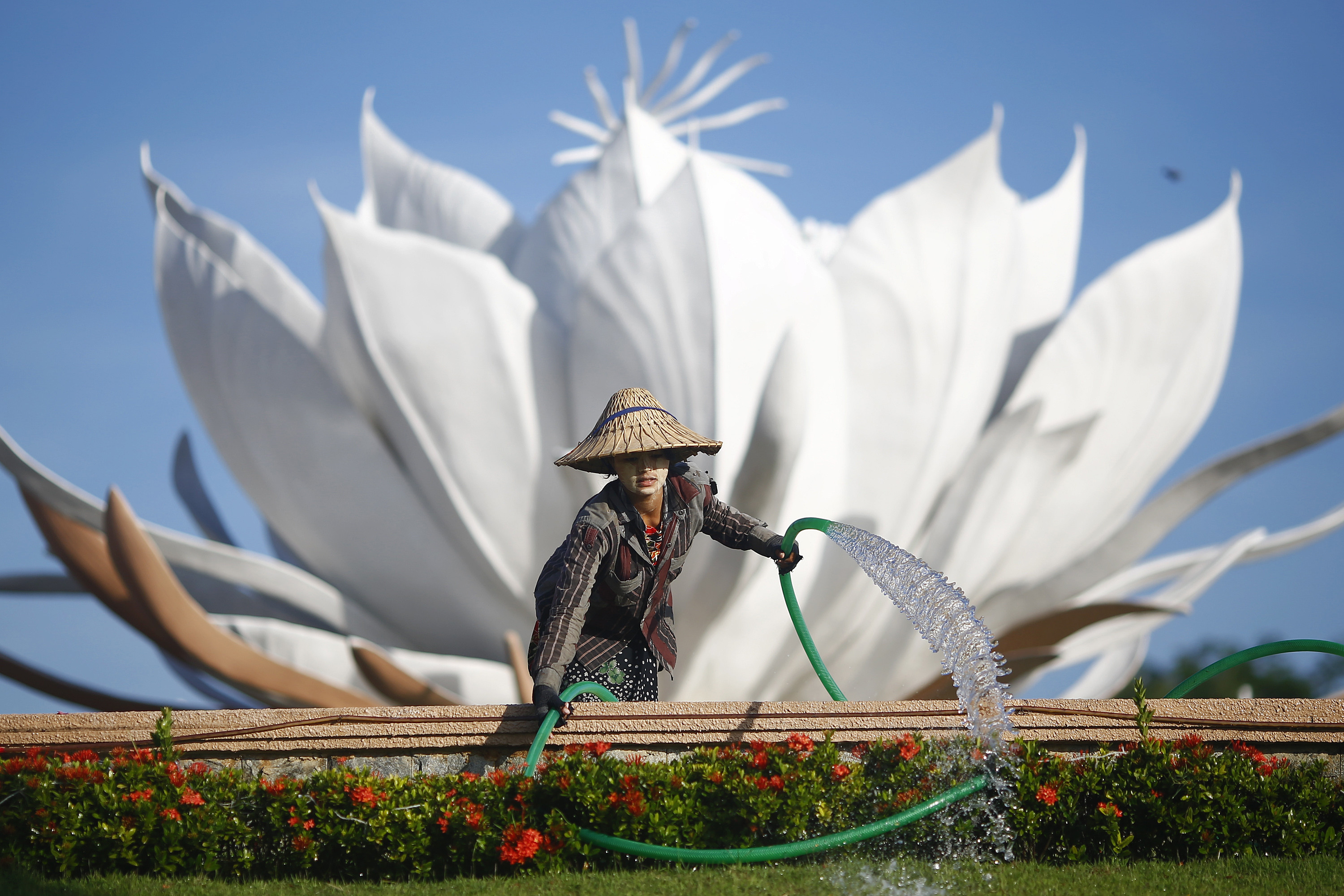 A female gardener waters flowers in Nay Pyi Taw, Myanmar.