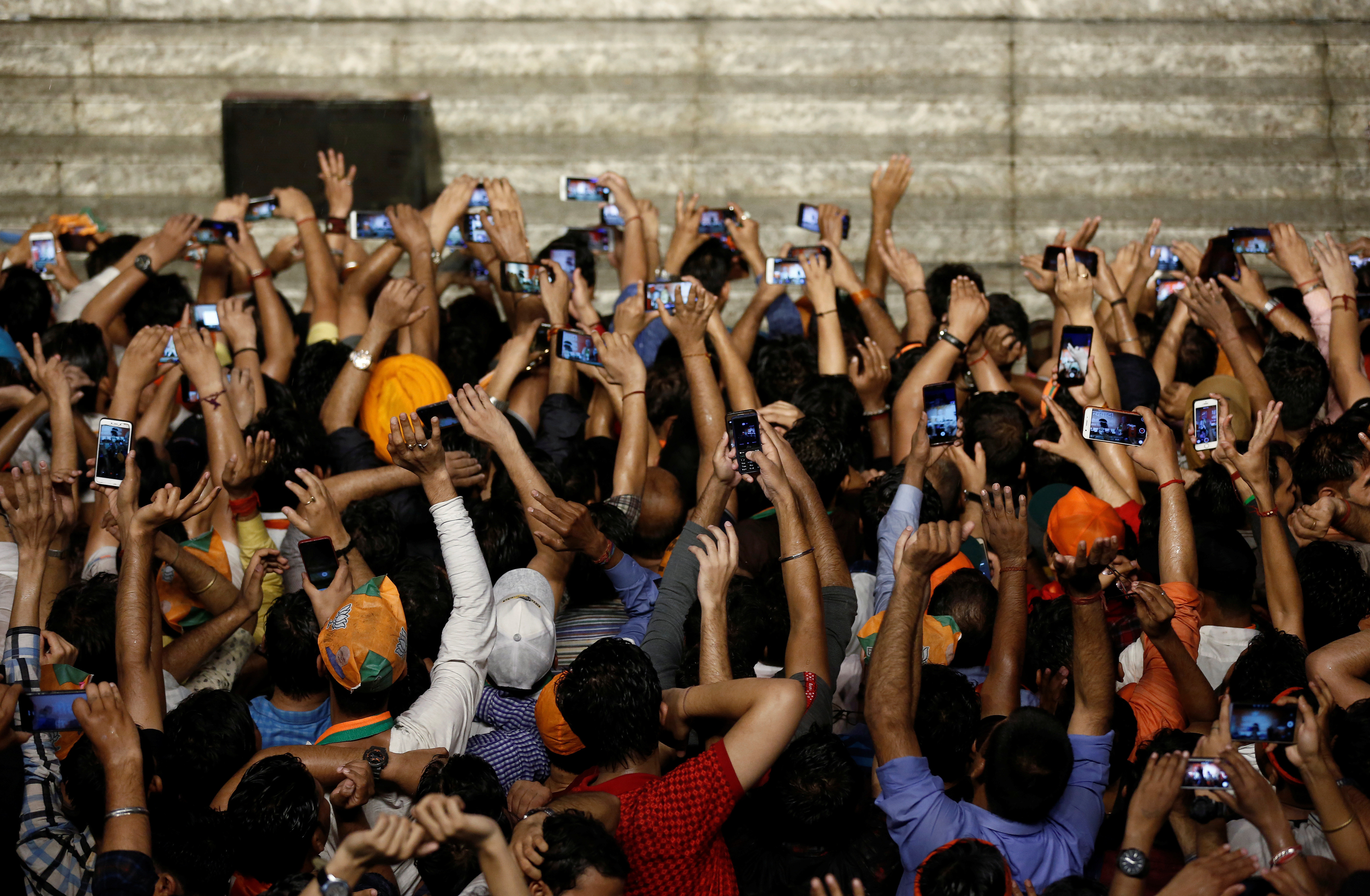 Supporters of Indian Prime Minister Narendra Modi use their mobile phones to click his pictures as he addresses them after the election results at the Bharatiya Janata Party (BJP) headquarter in New Delhi, India, May 23, 2019.