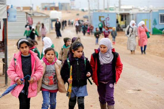 Syrian refugee children walk to school at the Al Za'atari refugee camp.