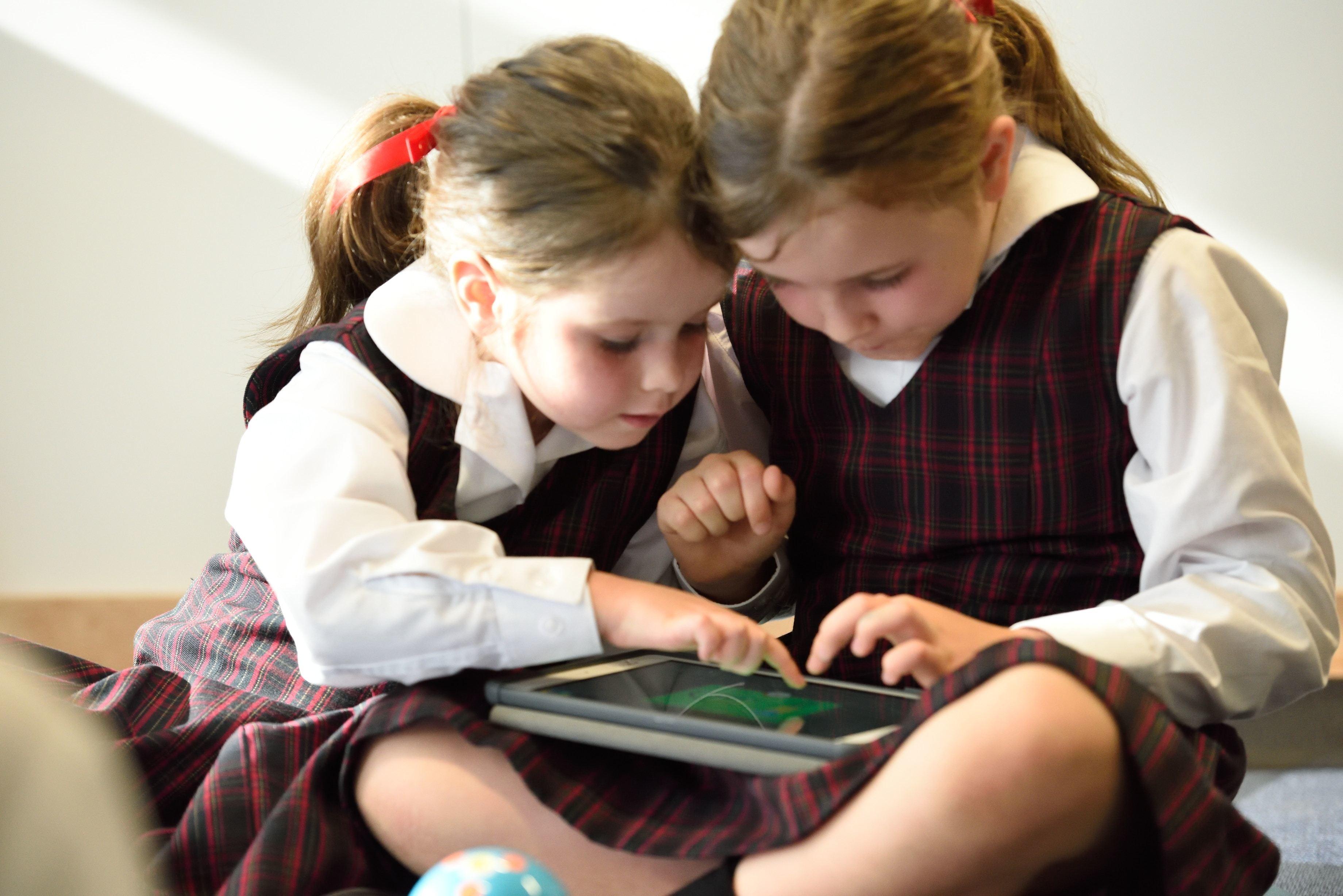 A good start … two schoolchildren use an iPad.