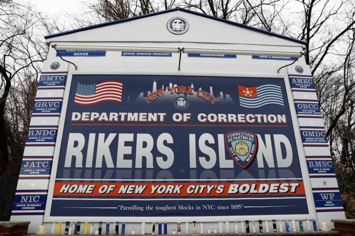 Candles are seen on the sign marking the entrance to the New York City Department of Corrections Rikers Island facility in Queens, in New York, U.S., February 14, 2018