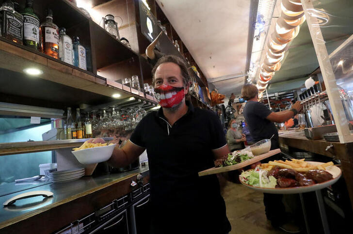 Jean, an employee at Inn R Green Restaurant hold dishes during the reopening after weeks of lockdown restrictions amid the coronavirus disease (COVID-19) outbreak, in Brussels, Belgium, June 8, 2020. REUTERS/Yves Herman