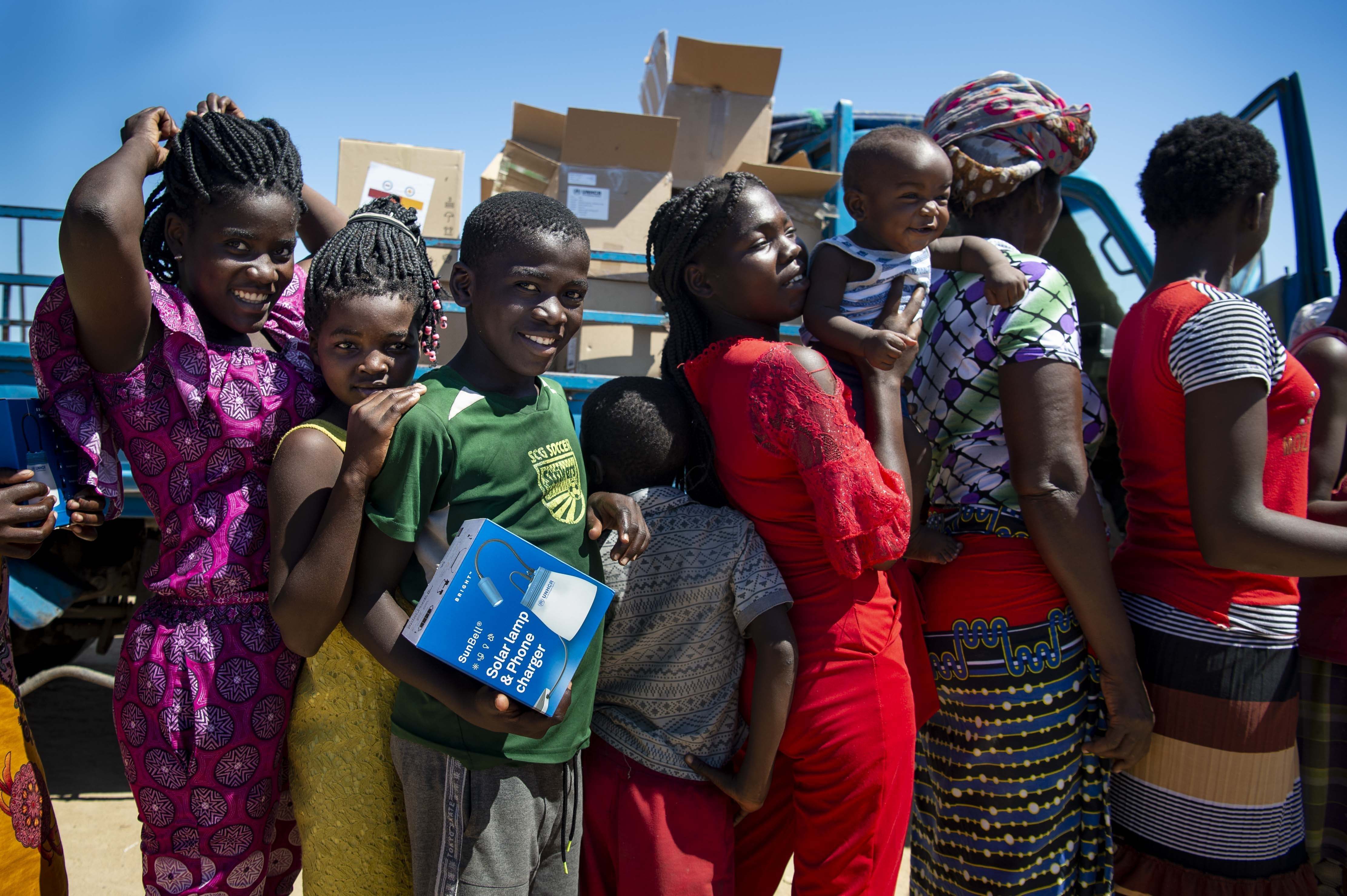Women and children wait in a food distribution line with new solar lanterns in hand.