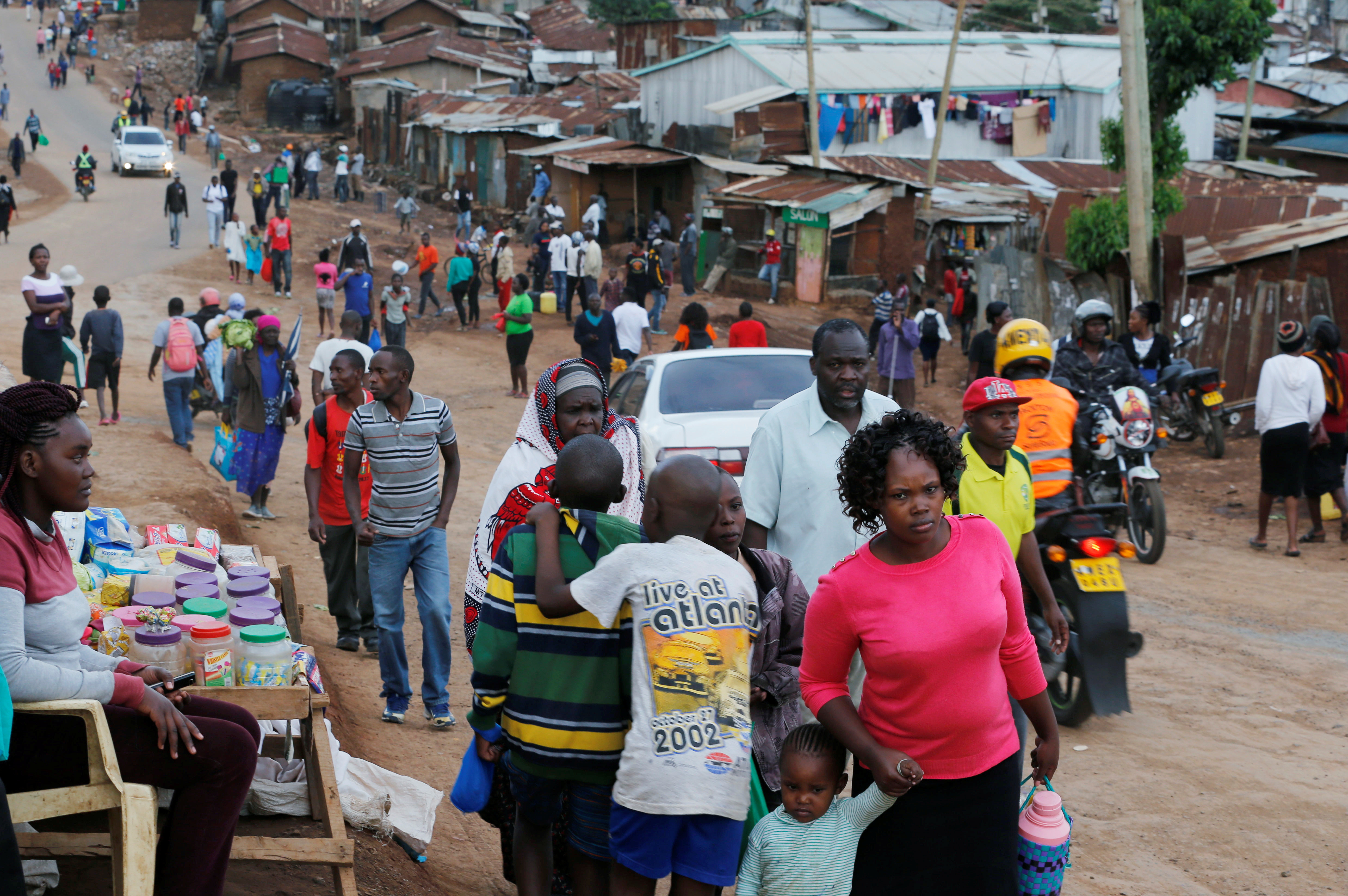 Civilians walk to their houses before a curfew which was ordered by the Kenya's President Uhuru Kenyatta to contain the spread of the coronavirus disease (COVID-19), within Kibera slums in Nairobi, Kenya March 27, 2020. REUTERS/Thomas Mukoya - RC2ISF9WVFQ6