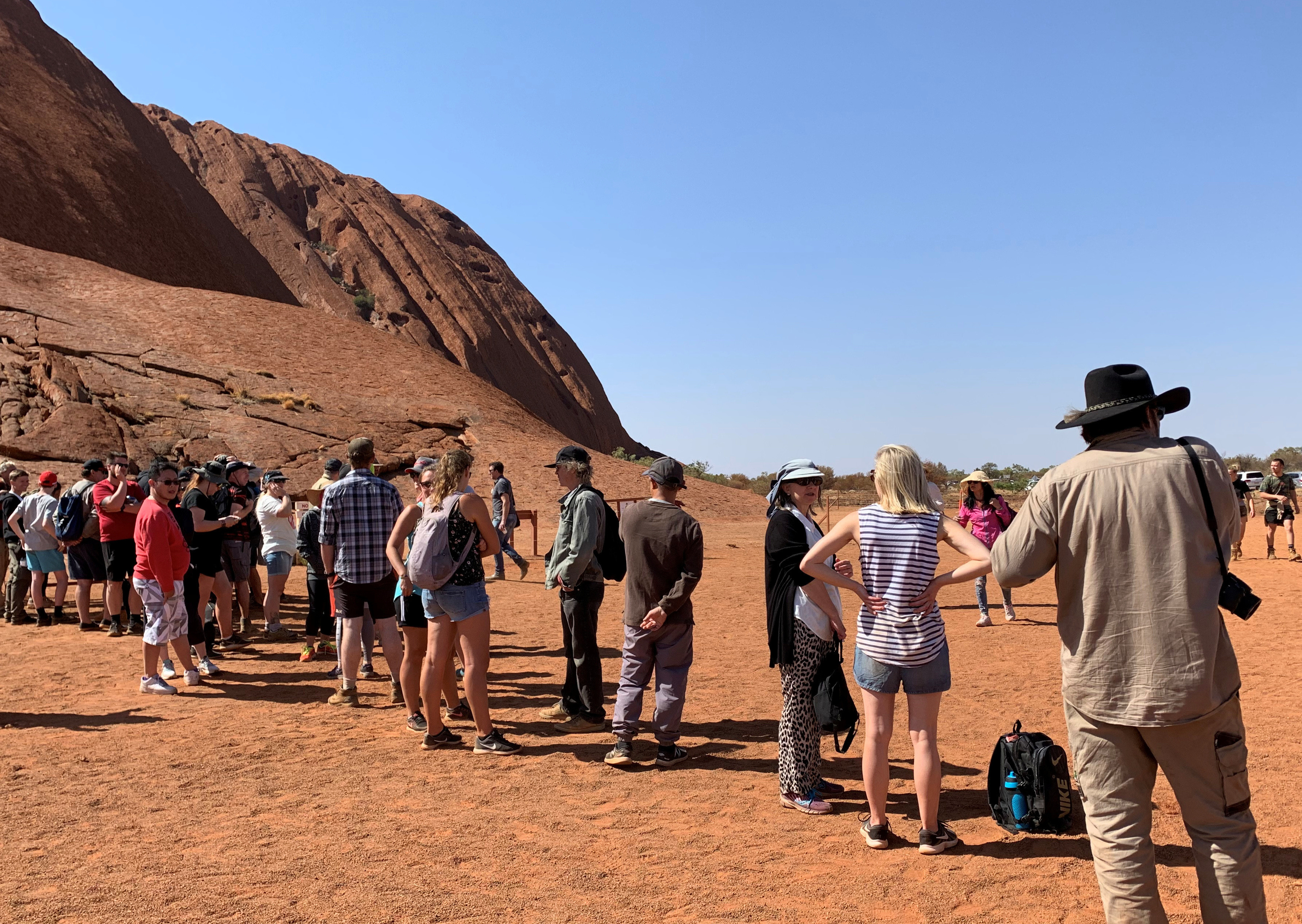 People line up to climb Uluru, formerly known as Ayers Rock, the day before a permanent ban on climbing the monolith takes effect following a decades-long fight by indigenous people to close the trek, near Yulara, Australia, October 25, 2019.