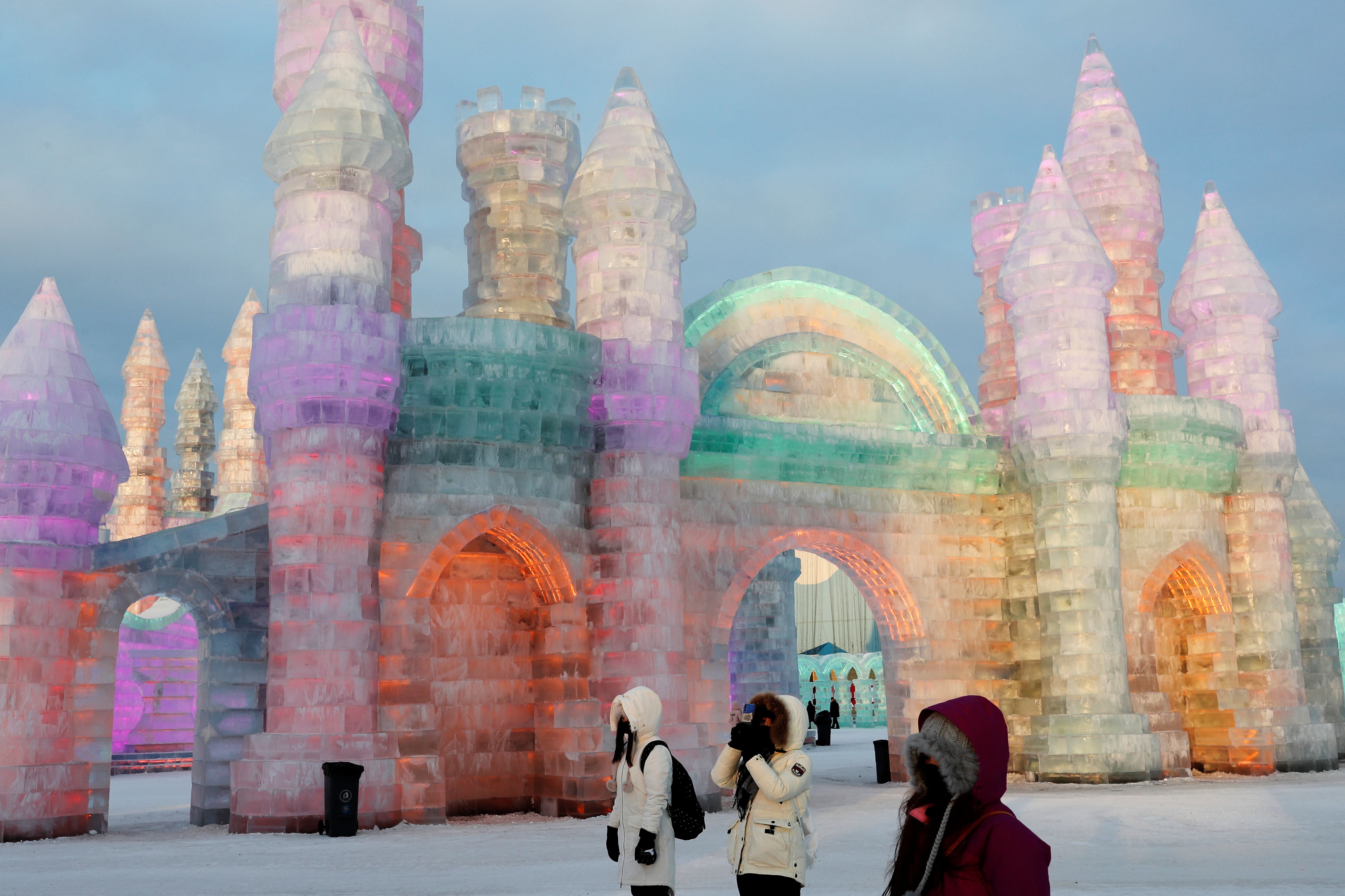 Visitors stand in front of ice sculptures illuminated by colored lights at annual ice festival, in the northern city of Harbin, Heilongjiang province, China January 4, 2019. REUTERS/Tyrone Siu - RC147AEFE4F0