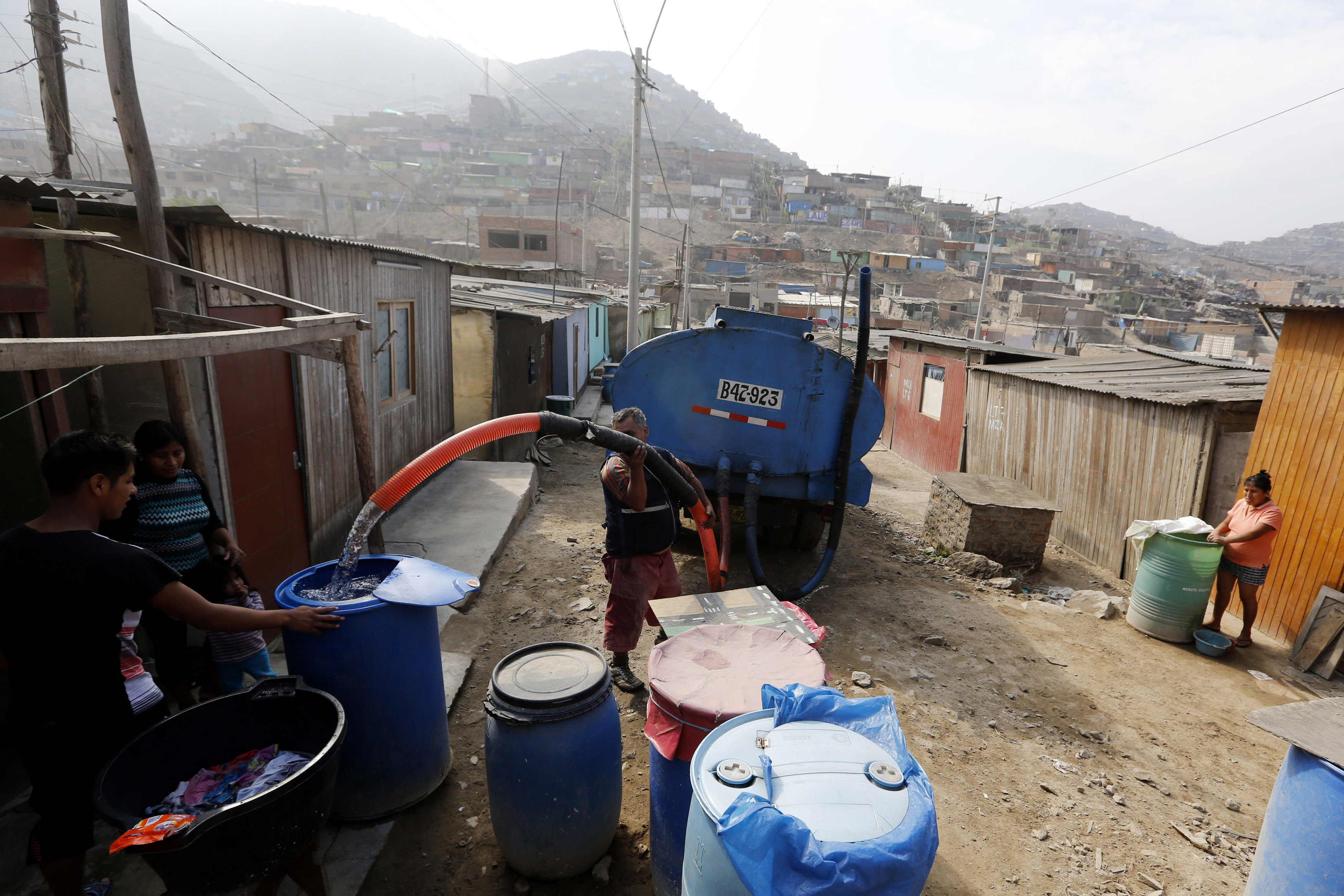 A man delivers water from a tanker in San Juan de Miraflores on the outskirts of Lima, Peru.