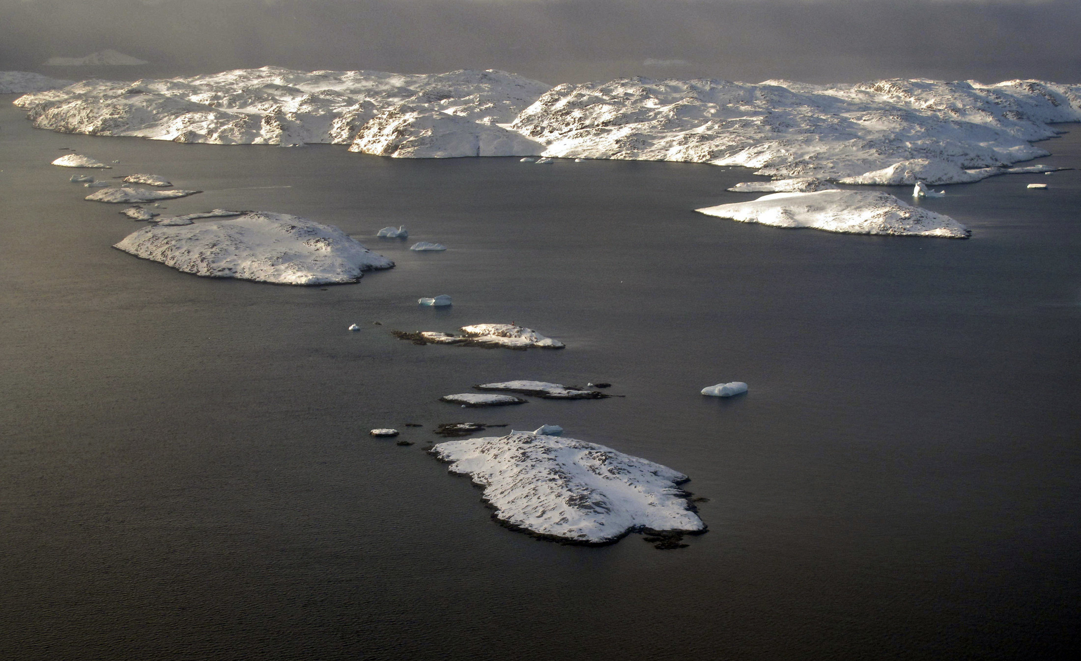 The snow-covered landscape is seen in an aerial photo near the town of Uummannaq in western Greenland March 17, 2010. Dutch artist Ap Verheggen plans to erect two giant sculptures on a piece of Greenland's sea ice and monitor them drifting away after the glacier breaks off.  REUTERS/Svebor Kranjc (GREENLAND - Tags: ENVIRONMENT ENTERTAINMENT) - GM1E63I09X801