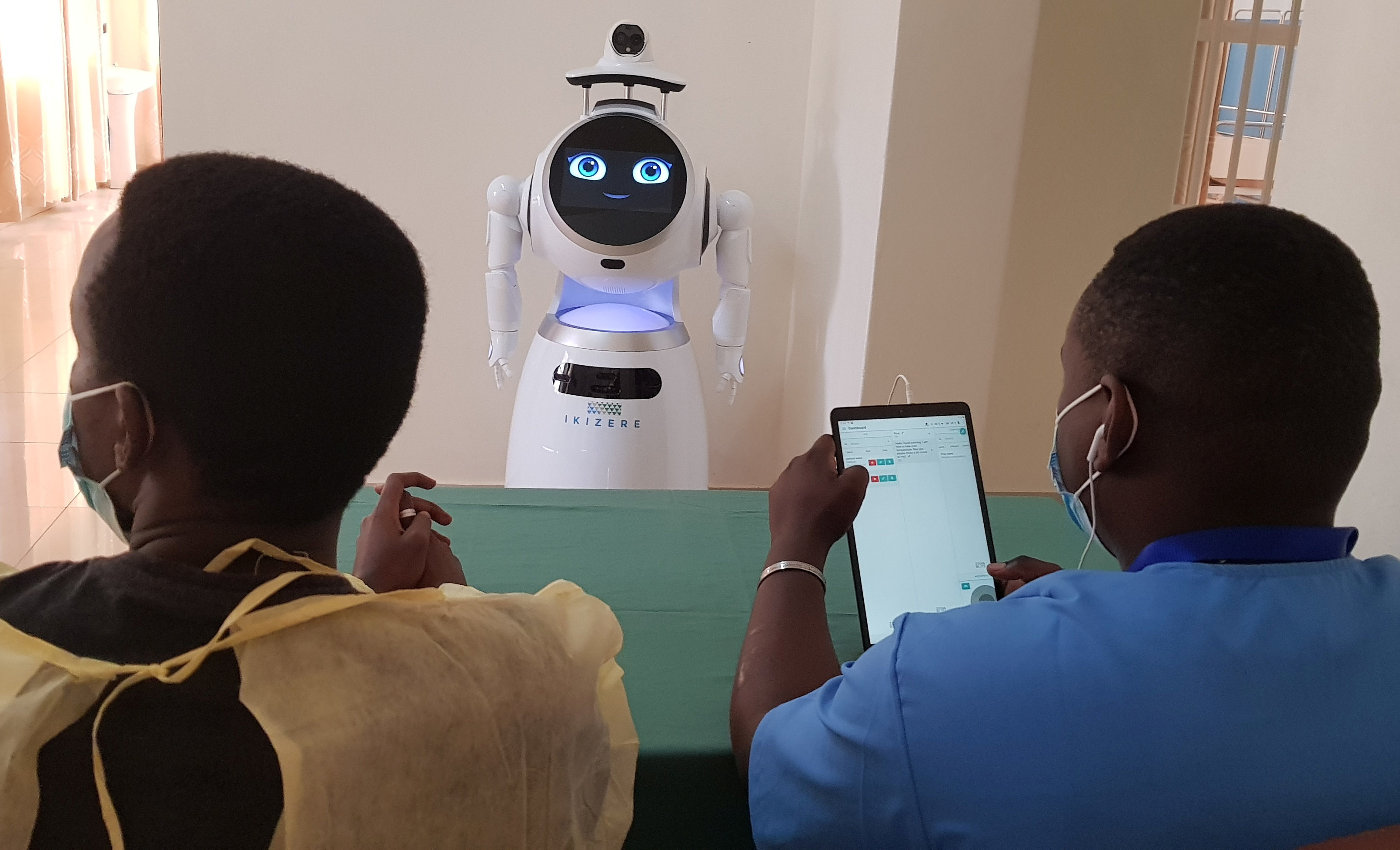 Engineers give instructions to a high-tech robot developed by Zora Bots, a Belgium-based company, and donated by the United Nations Development Program (UNDP) at the Kanyinya treatment centre that treats coronavirus disease (COVID-19) patients, in Kigali, Rwanda May 29, 2020. Picture taken May 29, 2020. REUTERS/Clement Uwiringiyimana - RC2XYG94DYBZ