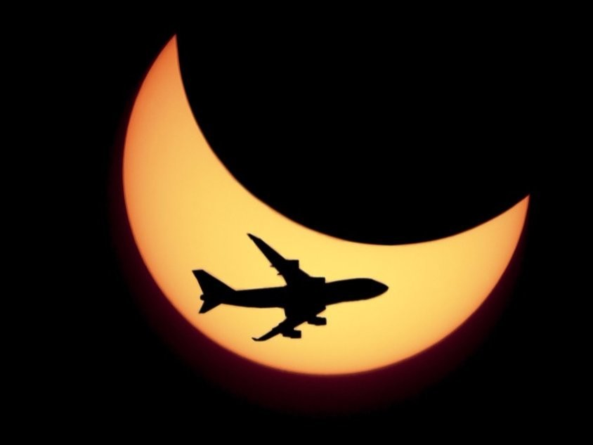 An airplane flies in front of the crescent of a solar eclipse.