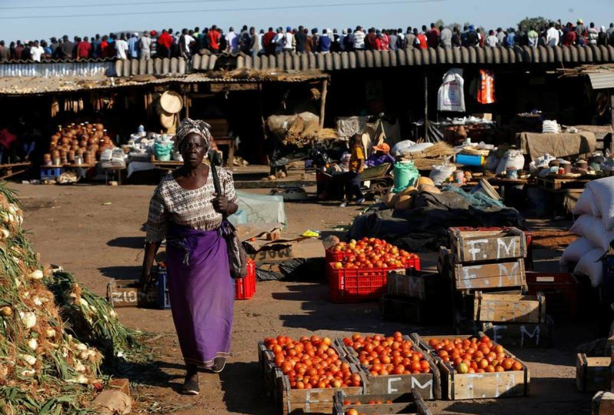 A women walks at a market while supporters of MDC, Zimbabwe's opposition party attend a rally in Bindura outside the capital Harare, Zimbabwe, July 27,2018.