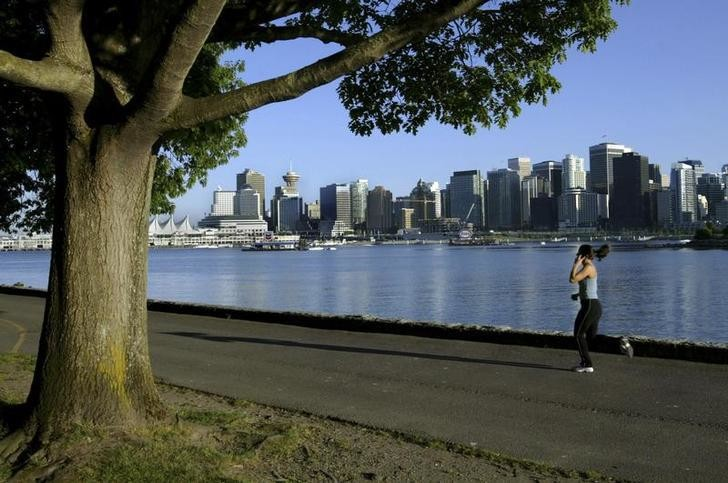 A jogger runs along the seawall in Stanley Park with the city skyline in the background in this June 24, 2003 file photo. Vancouver, host of this month's Winter Olympics, prides itself on being one of the world's most liveable cities but residents seem unsure at times whether they really want the world on their doorstep.   To match feature OLYMPICS/VANCOUVER   REUTERS/Andy Clark (CANADA - Tags: SPORT OLYMPICS SOCIETY CITYSCAPE)